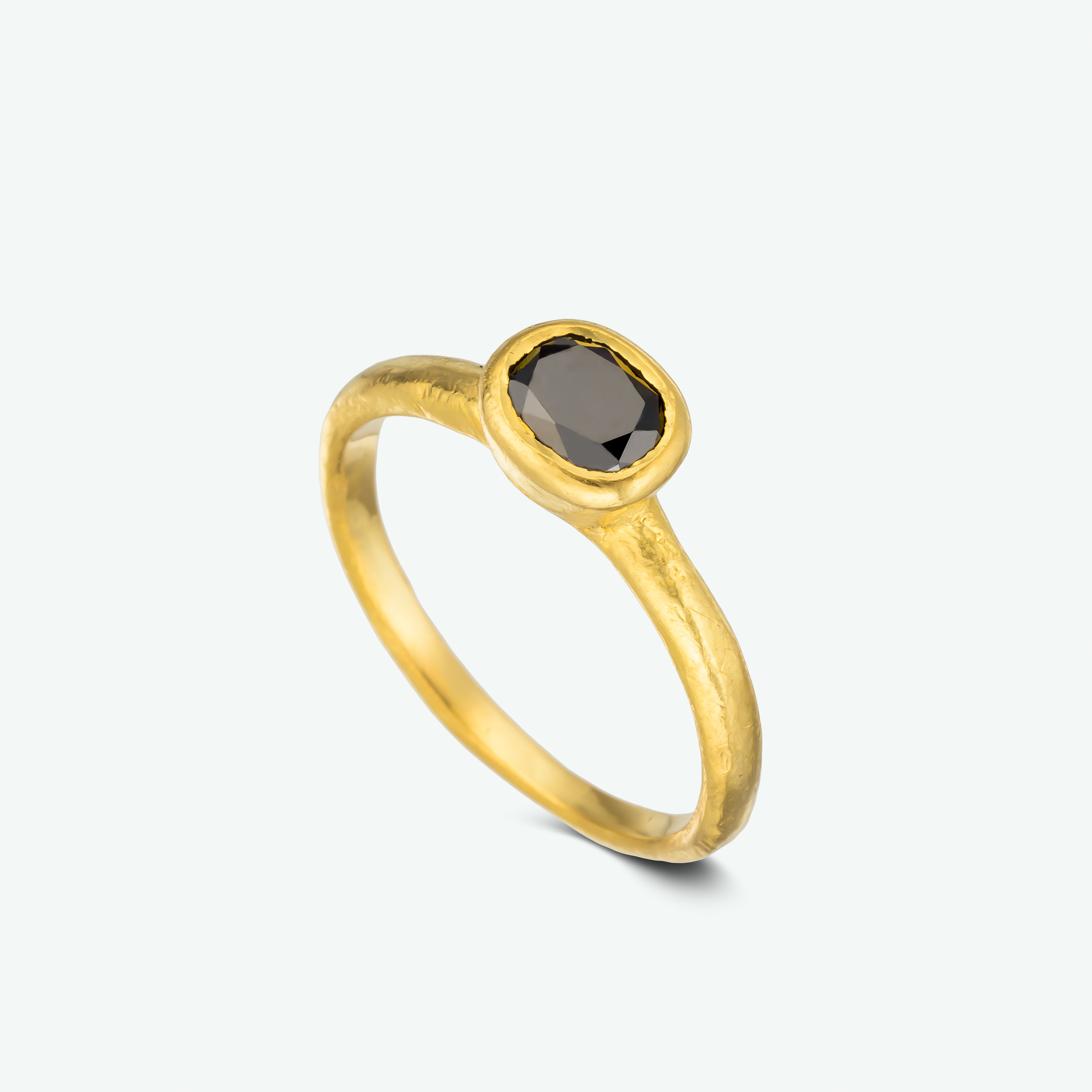 Rough and rustic was the theme while designing this unique engagement ring. Composed of 22k yellow gold and set with an oval black diamond. D: 1.00 ct.