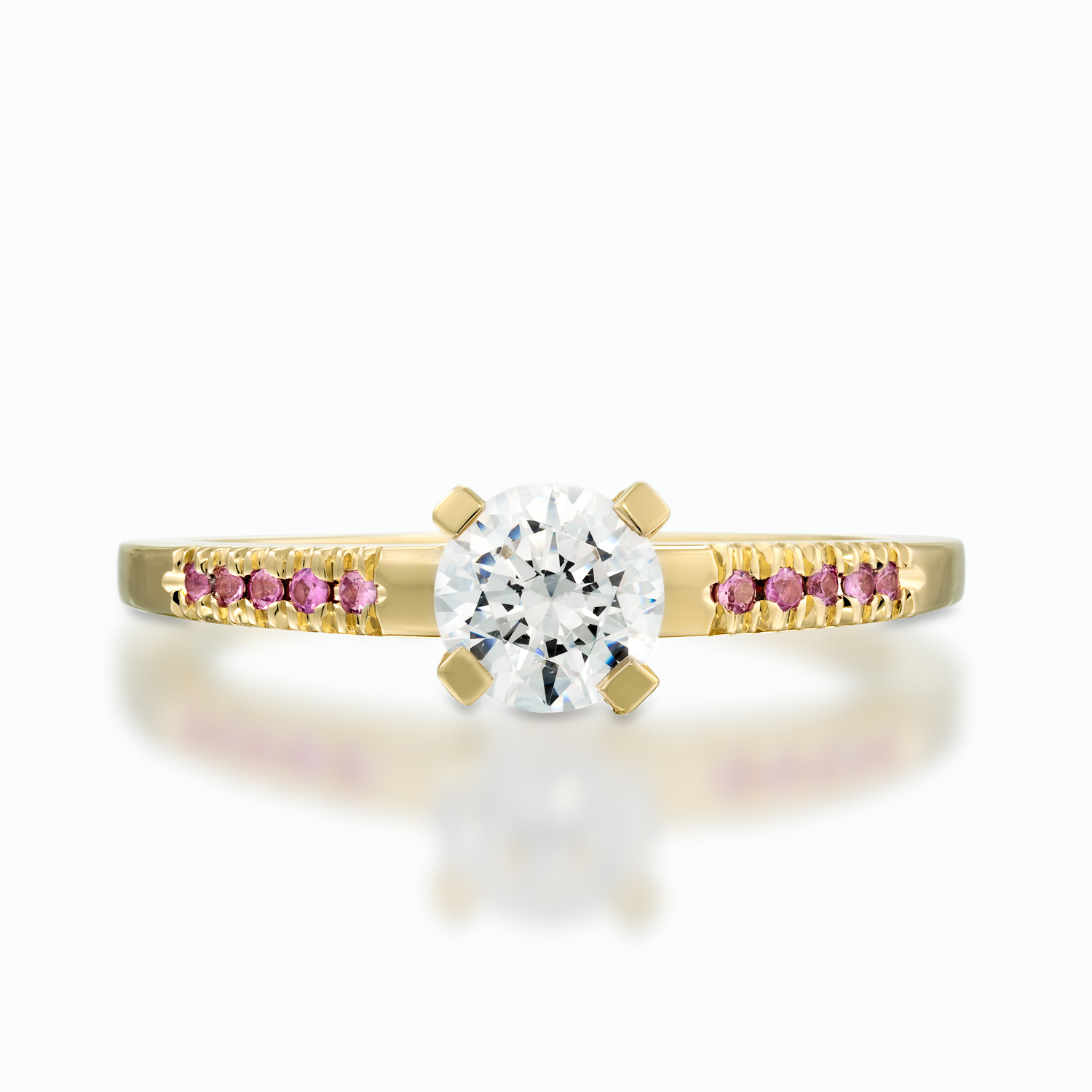 Classic yet unique solitaire engagement ring with a center setting of a diamond accented by pink sapphires on the sides of the band. D: 0.50-0.60 ct. PS: 0.06 ct.