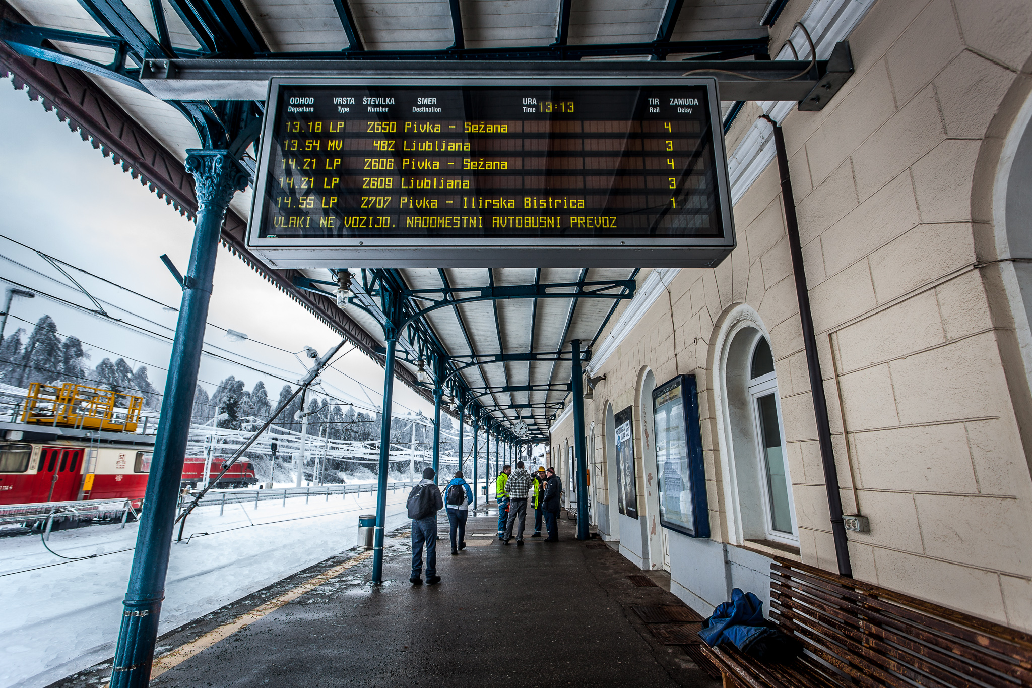 'Trains do not run. Substitute bus service' sign on the info-board at the Postojna train station. Workers are talking about repairing the tracks.