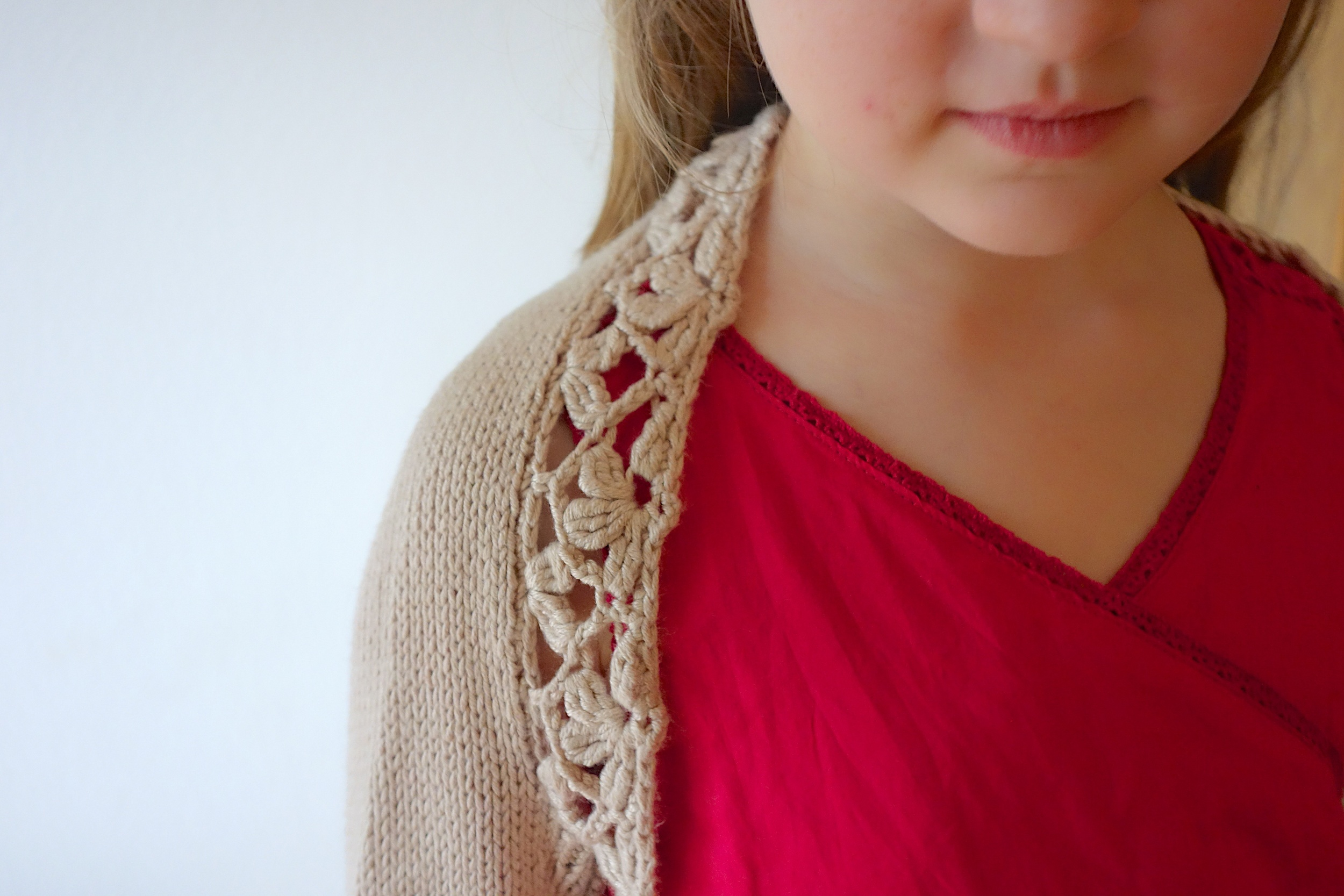 Flower Flower  shrug, sized from toddler to teen, is quick to knit in DK yarn and finished with a beautiful crochet lace trim.   Buy now.