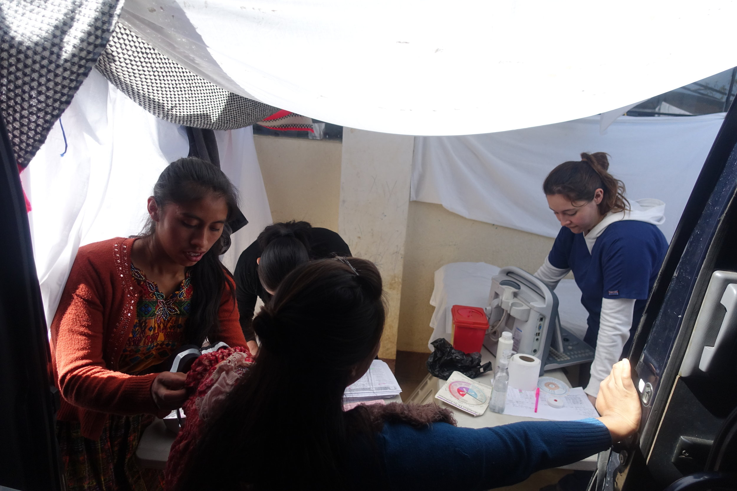 Midwives work with a patient at the mobile clinic.