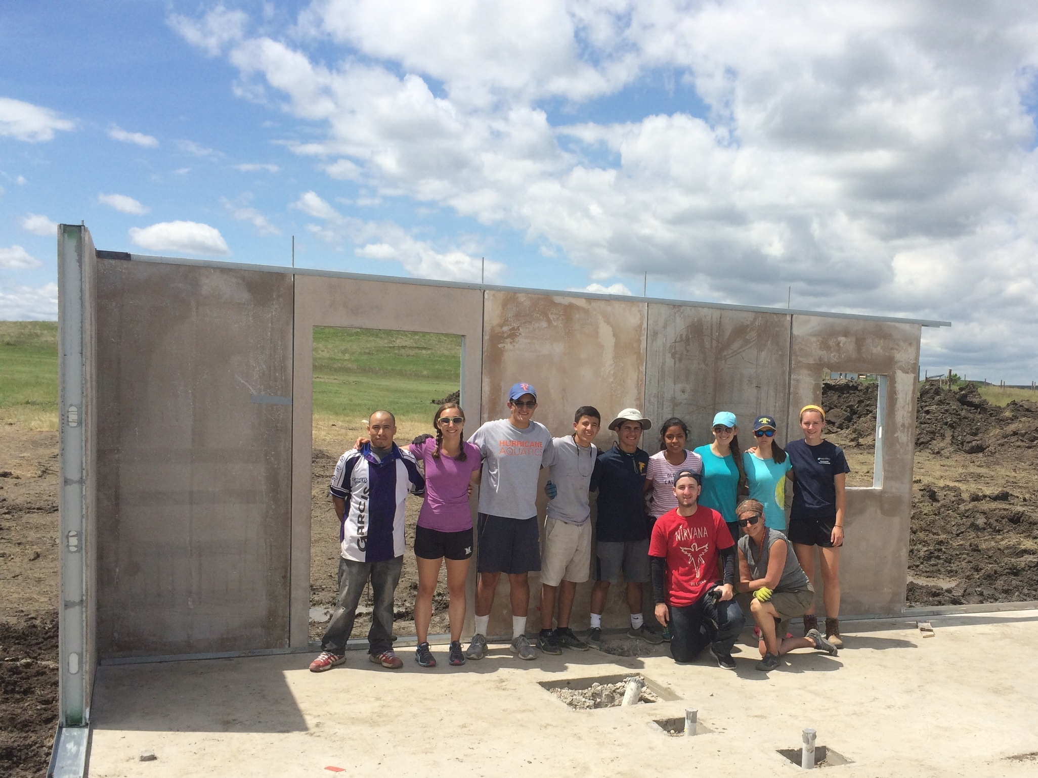 Many hands:  The Palmer Trinity School crew helped to install six wall panels on a new home for a great family in La Plant!