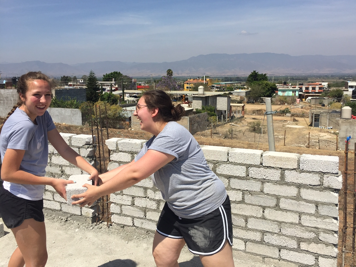 Camryn (left) and fellow volunteer, Katherine, pass cement bricks for an expansion of a patio at Casa Hogar Simply Smiles.