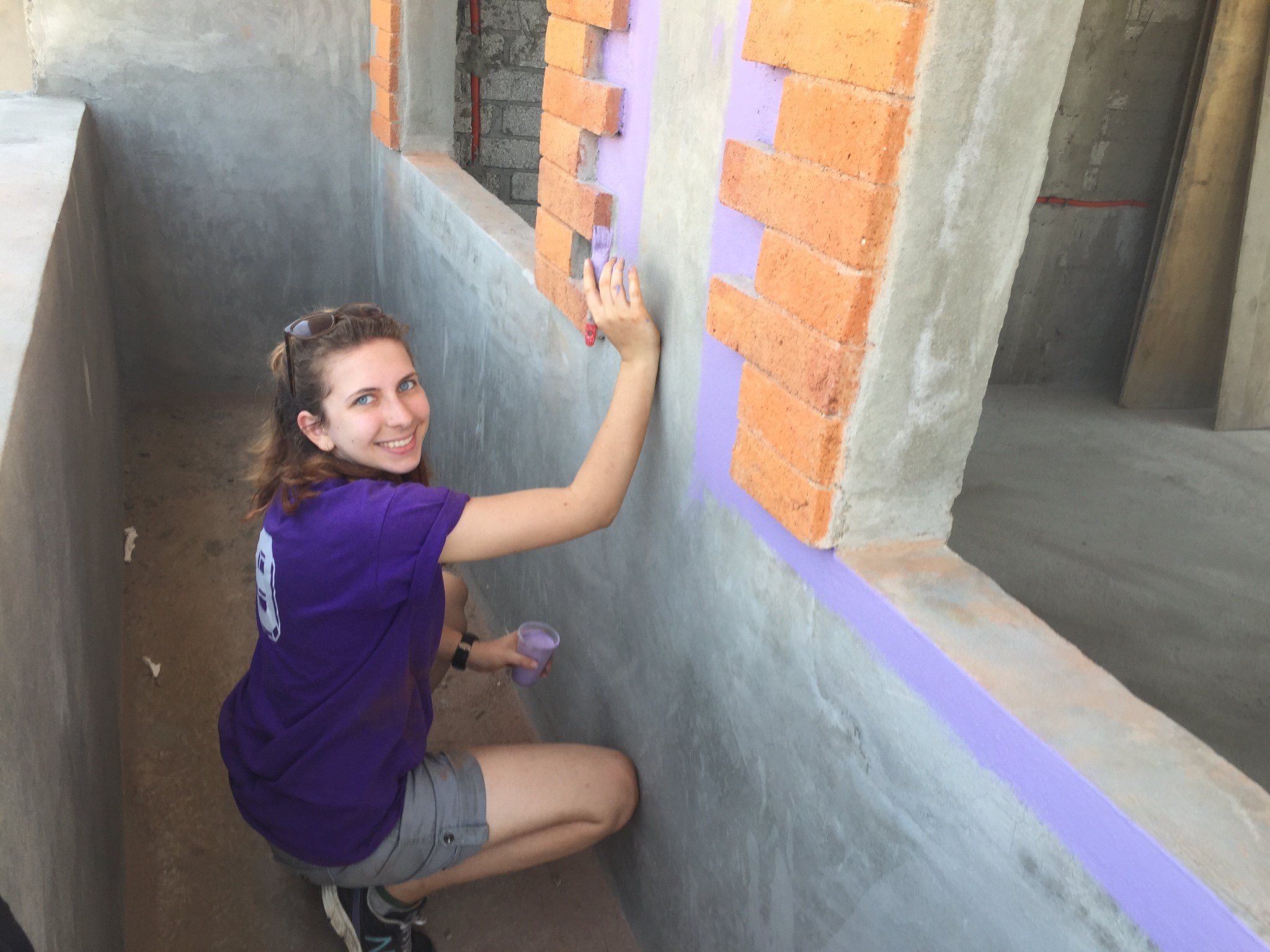Danielle paints the exterior of a new laundry room at Casa Hogar Simply Smiles.