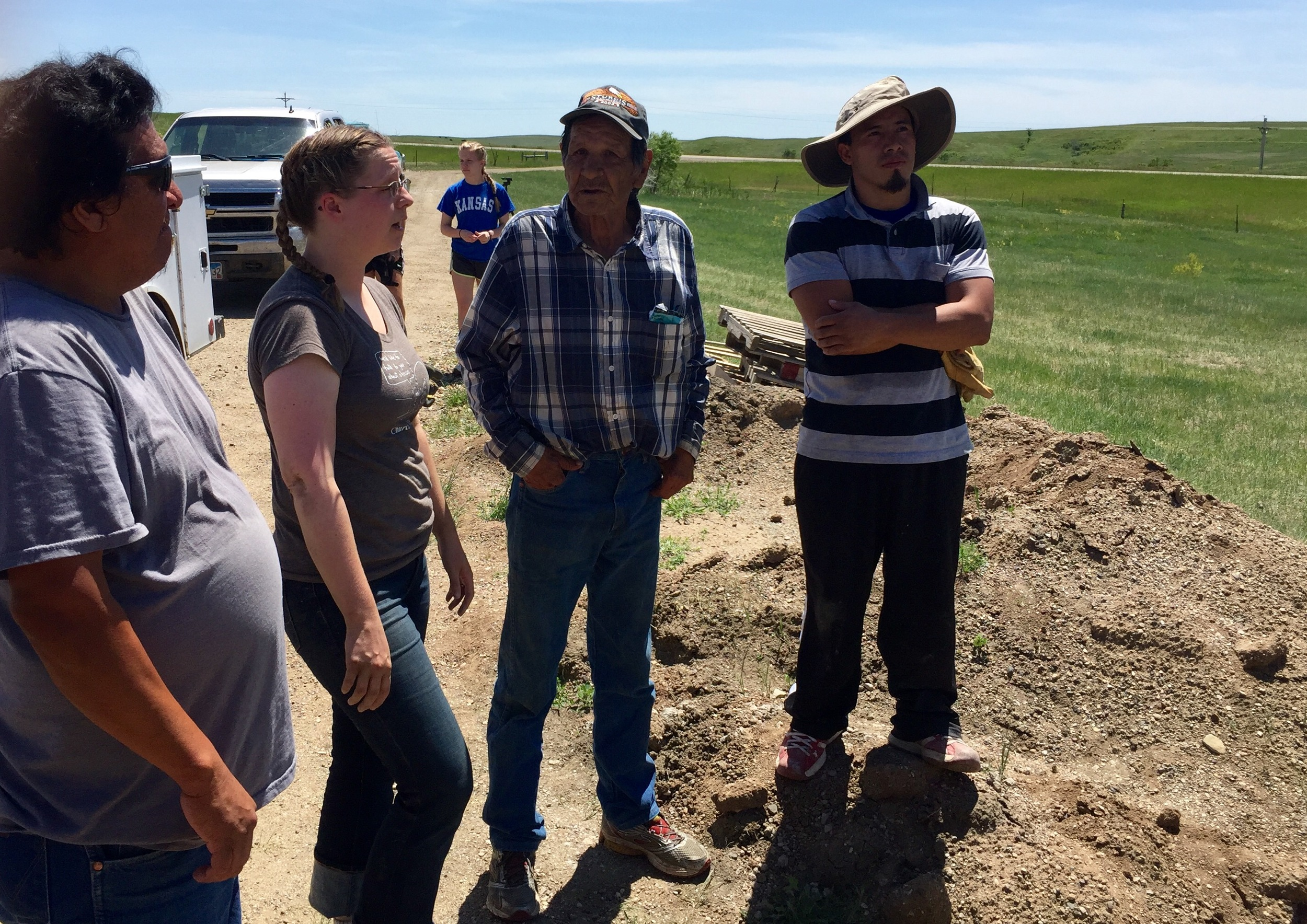 Plymouth Leader Eleanor (second from left) speaks with the housing recipients - Kee, Ford, and Elvis - at the housing site of Ford (second from right).