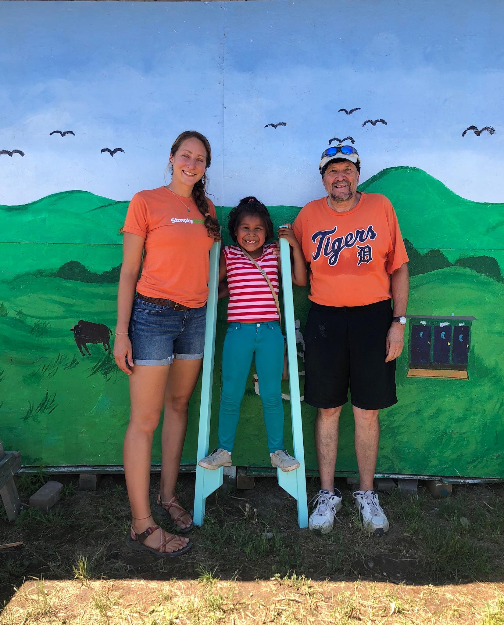 A little help from friends:  Simply Smiles Volunteer Coordinator Sam Steinmetz and her high school basketball coach Al Ciarlo, who has volunteered on the Cheyenne River Sioux Tribe Reservation, help their young friend balance on newly constructed stilts at Simply Smiles Summer Camp.