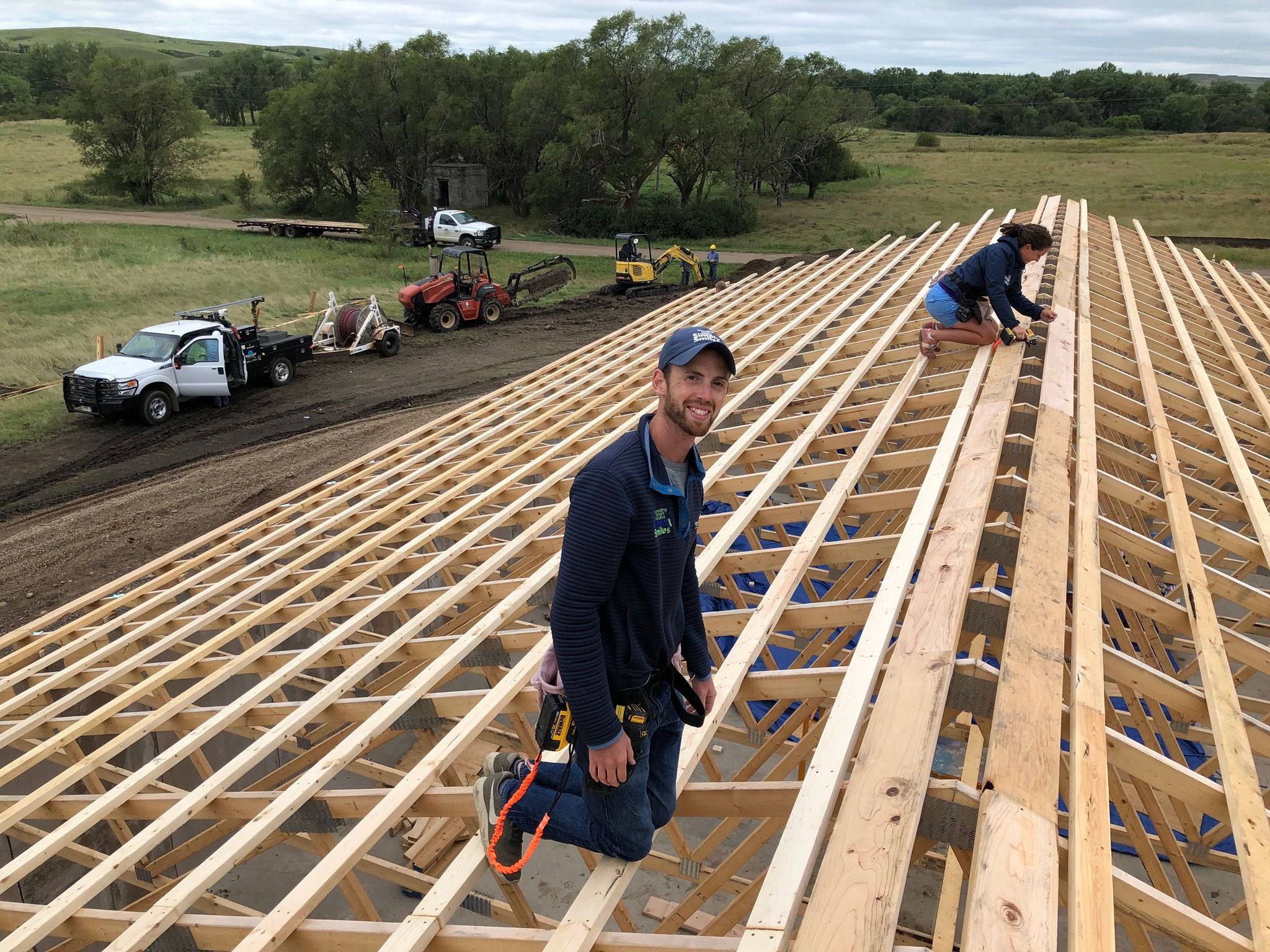 8/13/19: Simply Smiles staff members are hands on throughout the construction progress. Here, Zach and Kristen continue spacing of the purlins for the roof. The building is taking shape!