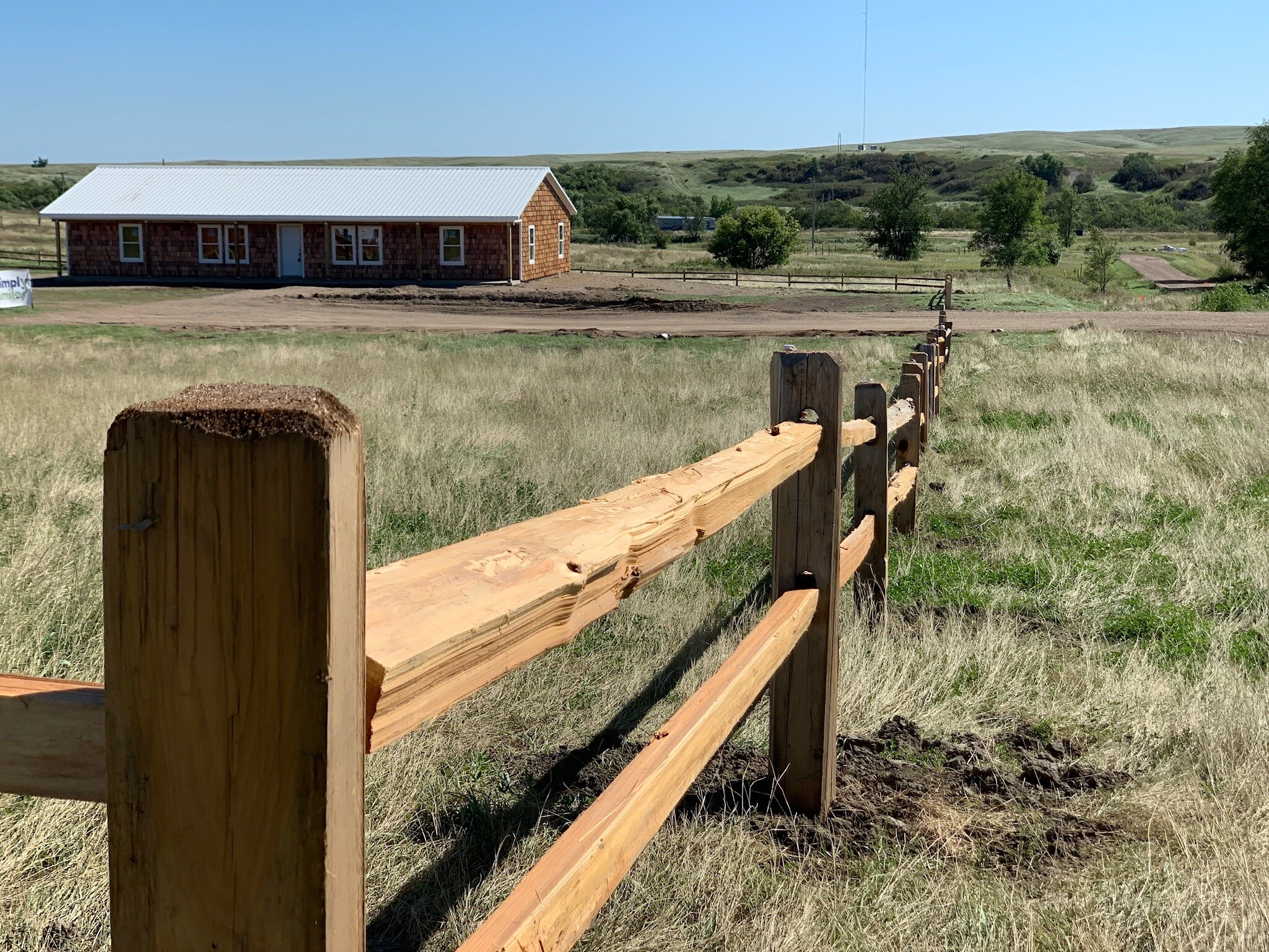 A view of the split rail fence and the approach road to the Simply Smiles Children's Village
