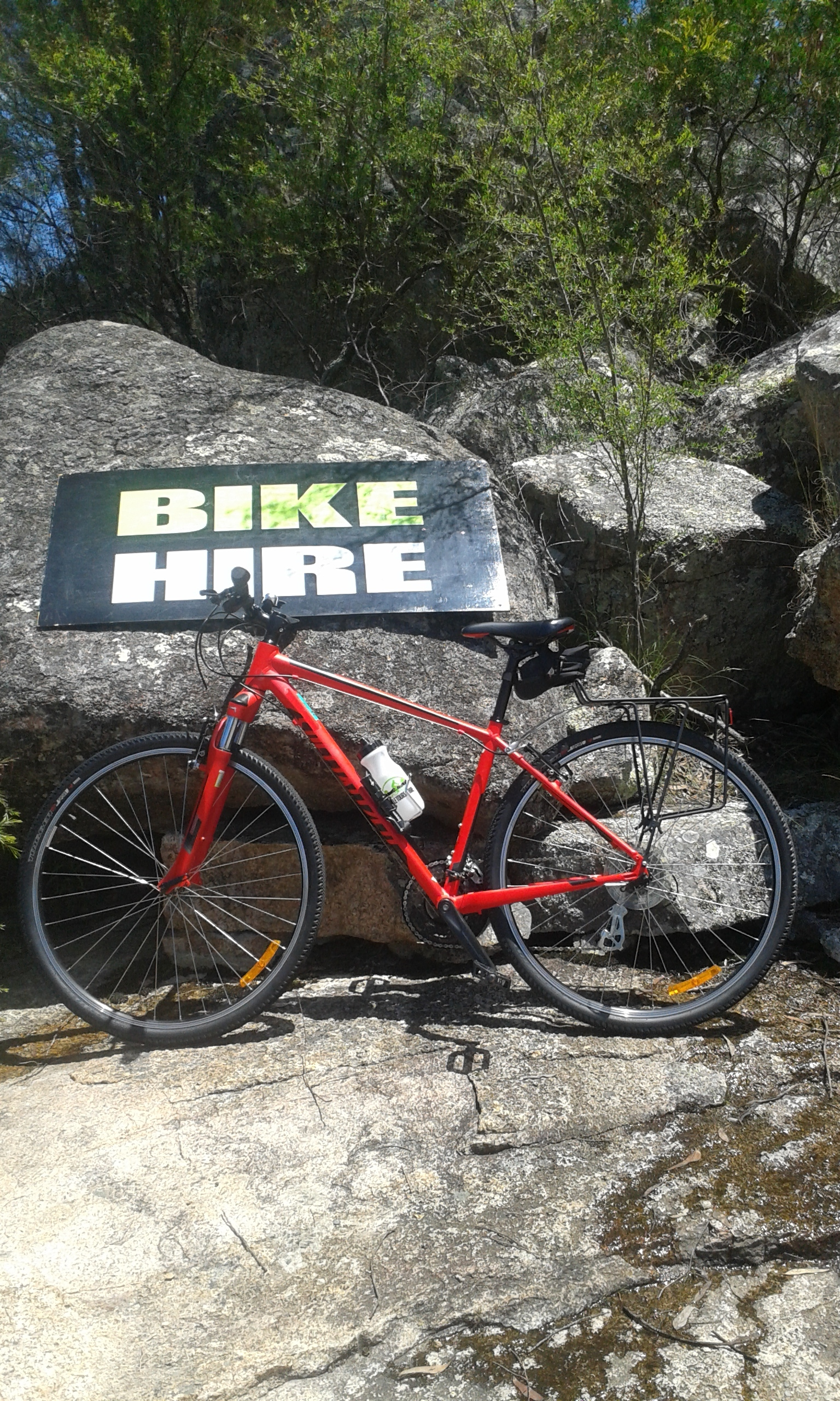 Red Specialized Crosstrail leaning again granite rock with bike hire sign behind.