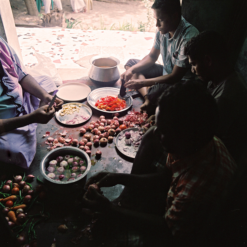 "A group of people, including several kothis prepare food at Sivagami's house. For many of the kothis, who live with their families, being able to prepare and serve food – considered to be ""women's work"" is a way for them to express part of their female identity. November, 2013"