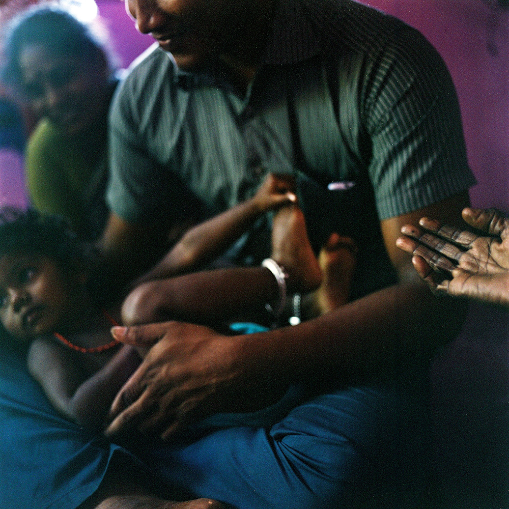 Mohana holds her niece while sitting with her family in their house in the village of Devanapattinam. November 2013