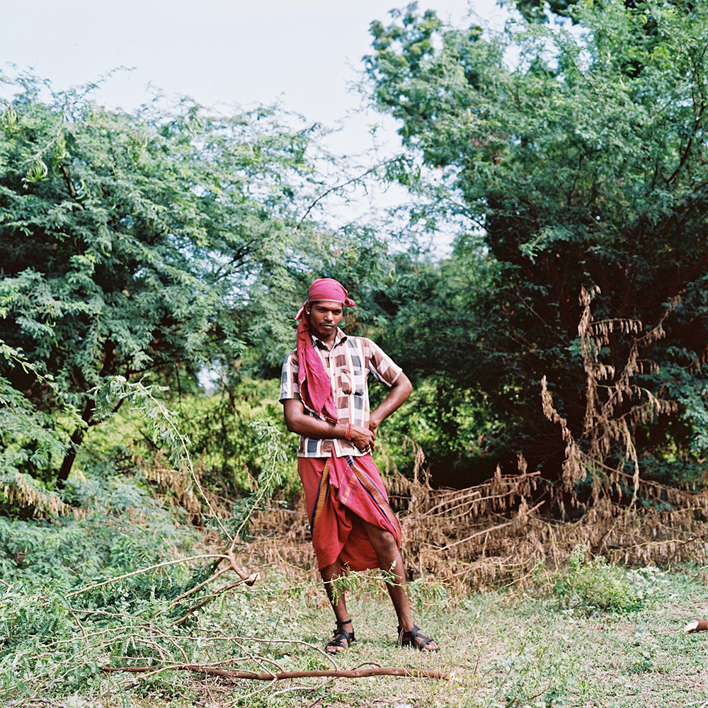 Chitra, a kothi priest from outside of Cuddalore, poses for a portrait while cutting down wood used for cooking. Many kothis choose to do this kind of work – which is traditionally done by women – as another way to express their female identity. November 2013.