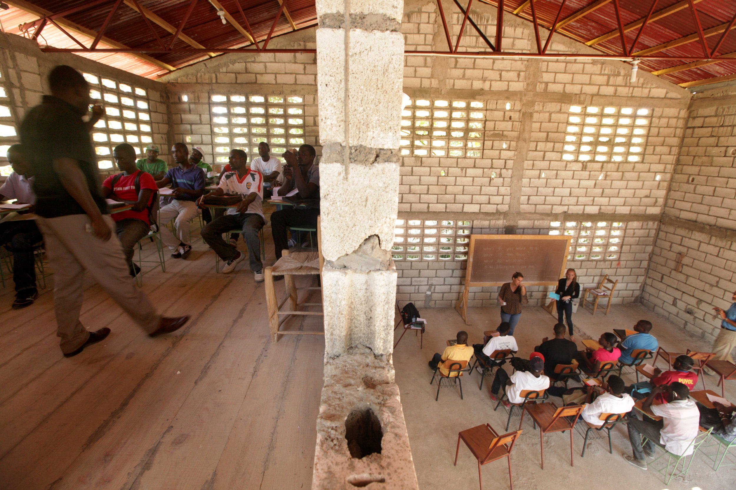 Rithot Thilus, left, teaches a class on business skills at Groupe d'Accord Solidarité Action professional trade school.