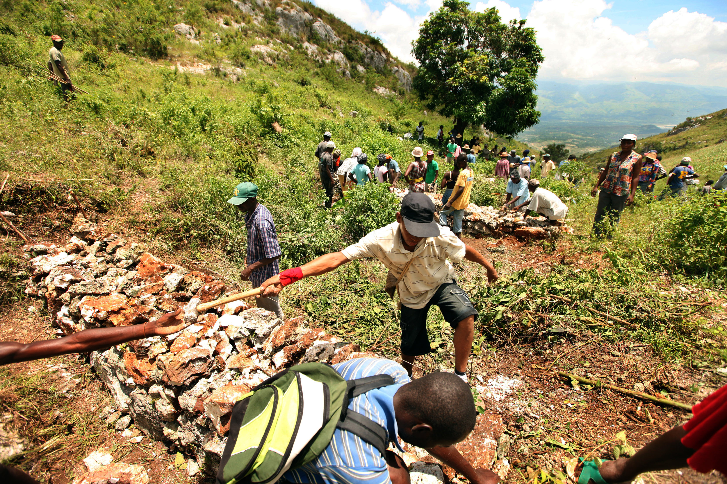 The Desarmes Development Organization partnered with MCC to construct stone retaining walls that will conserve soil and protect the water supply of Desarmes, the town below.