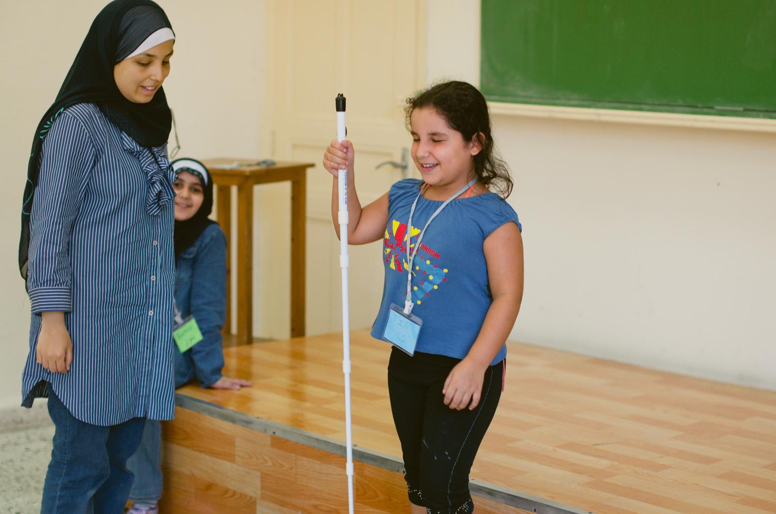 Sara Minkara (left) supervises a girl learning how to use a white cane.