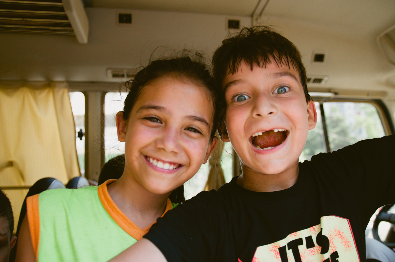 A girl (left) and a boy (right) smile for the camera.