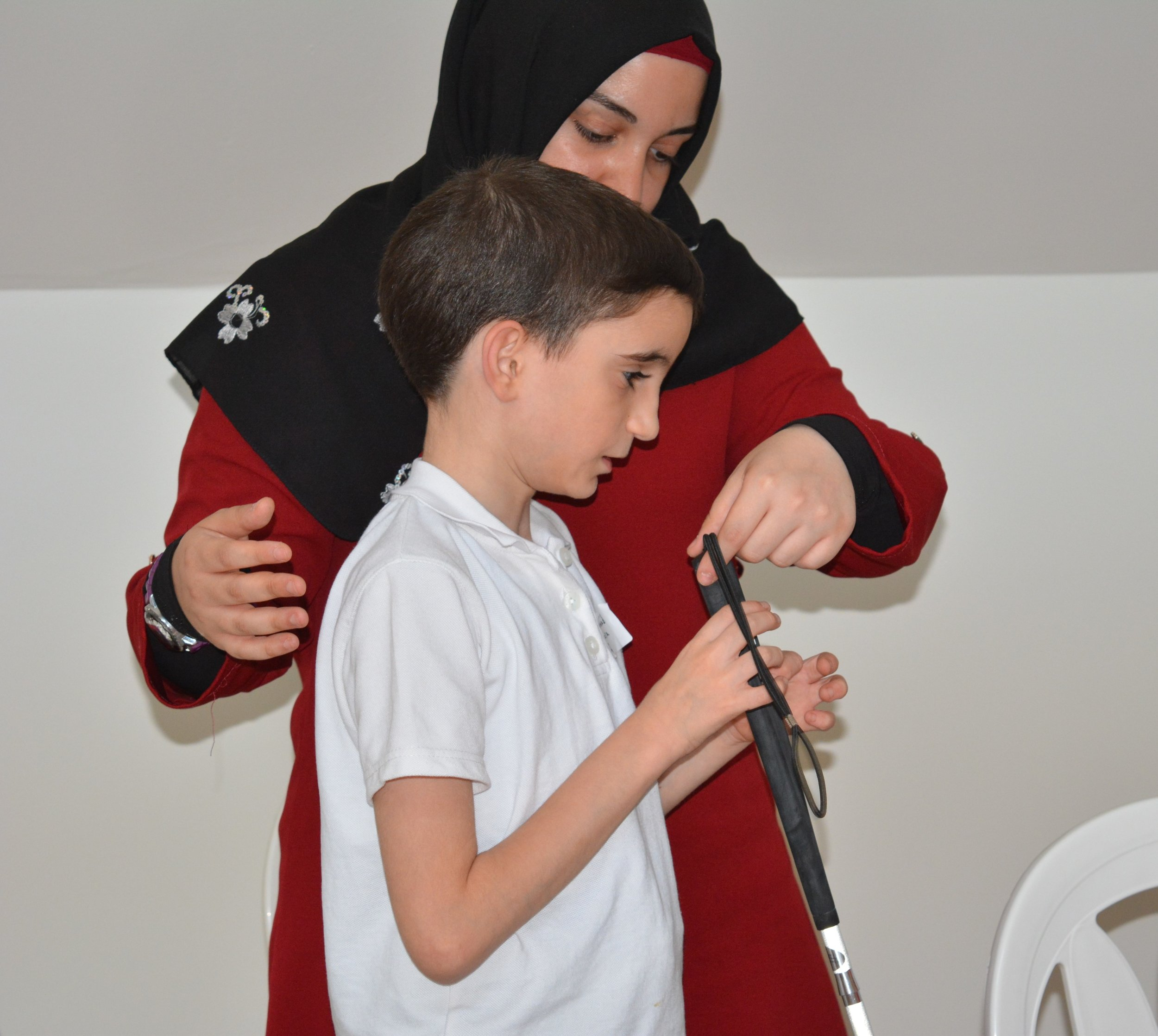 In the picture: a child learns how to hold a white cane.
