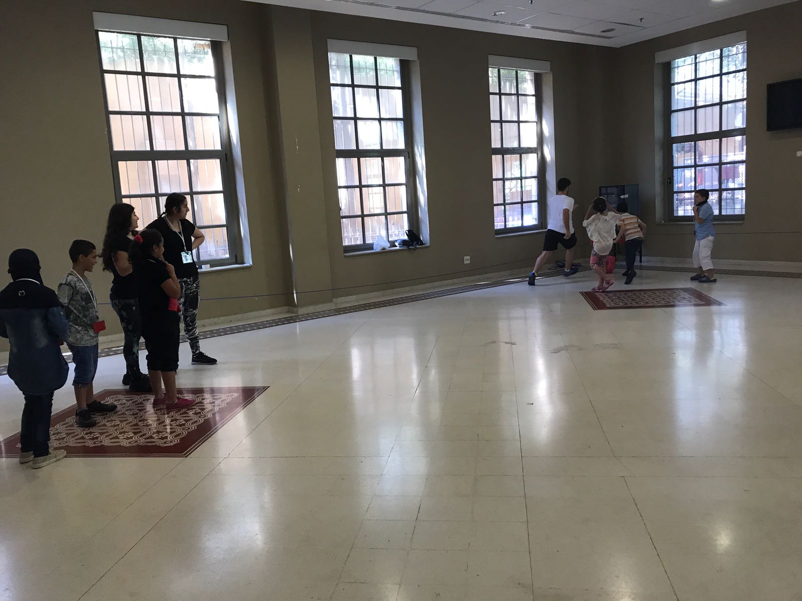 In the picture: a group of about four children, to the left, watch a group of about four other children, to the right, practice a soccer drill in the corner of an open room while a volunteer supervises.