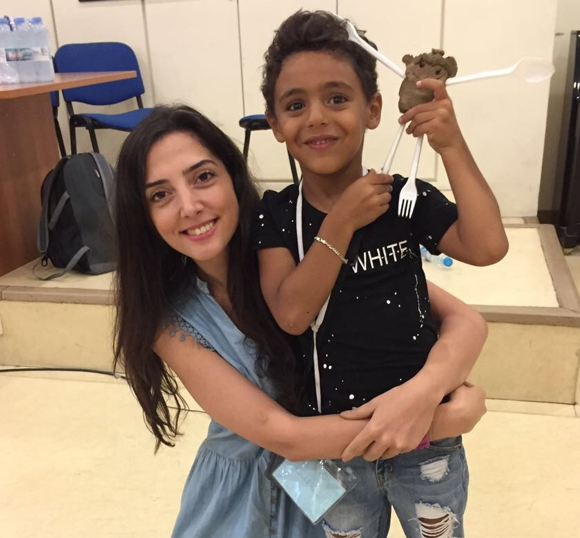 In this photo: Rania, ETI art class trainer (left) poses with a camp participant, who is showing off his sculpture; she wraps her arms around his waist.