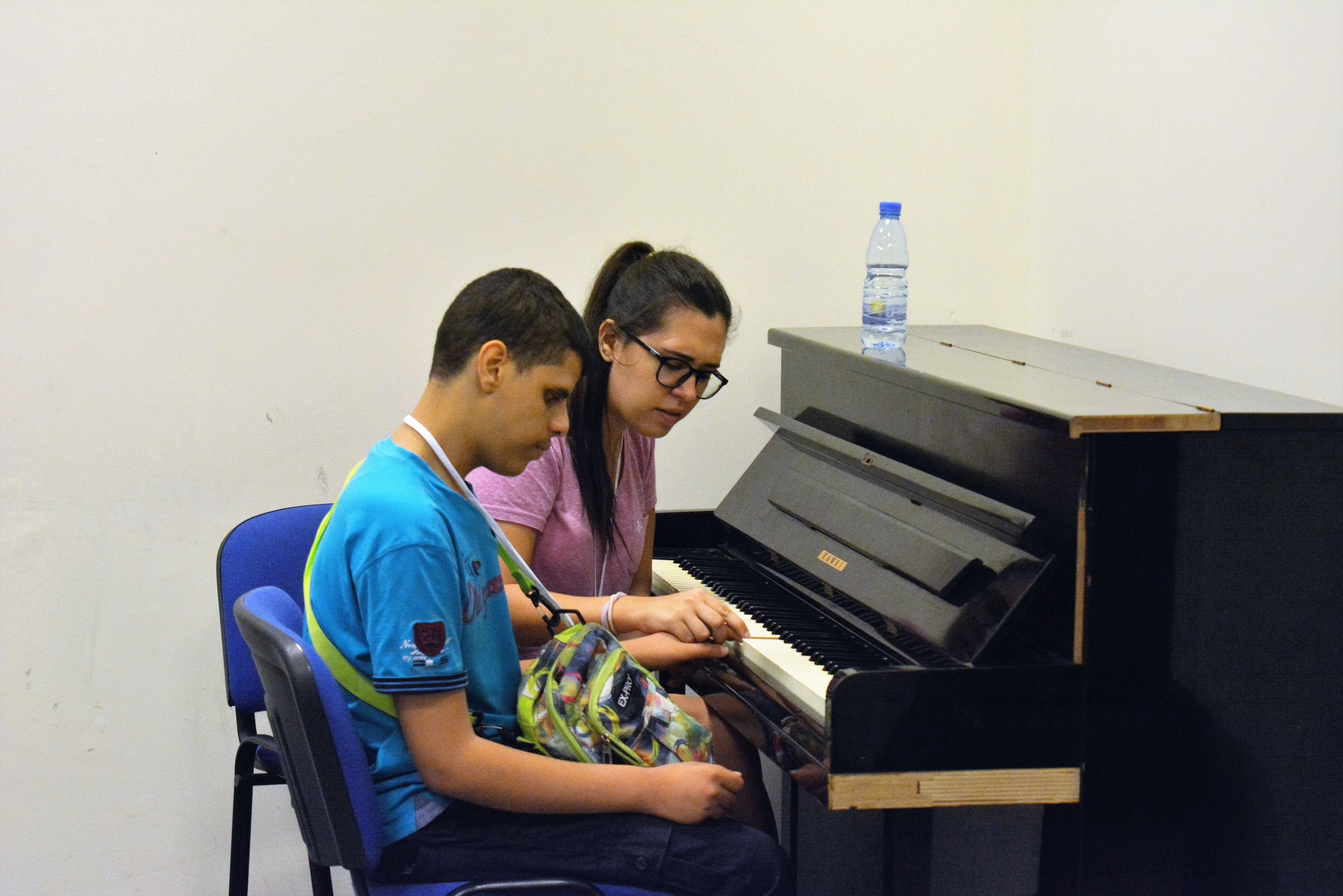 In the picture: a music teacher sits to the left of a participant with visual impairment at a piano and guides his hands on the keys.