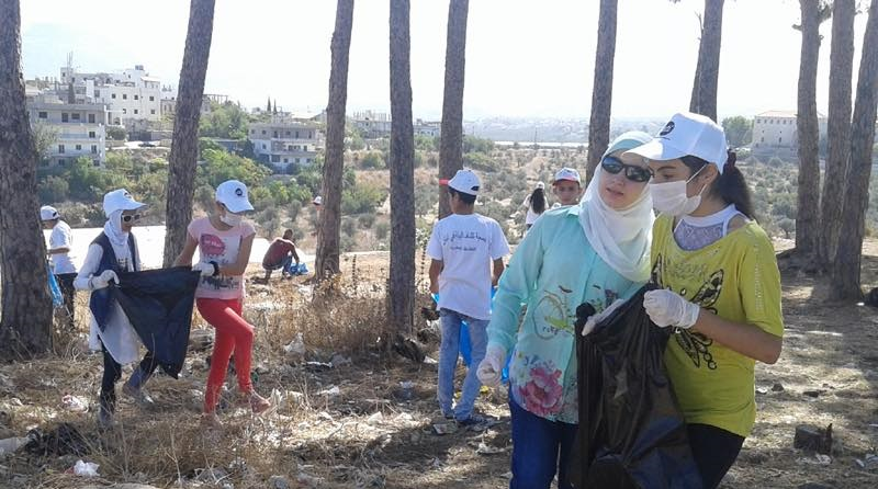 In the picture: a group of volunteers gather plastic items to be recycled using trash bags in a wooded area.