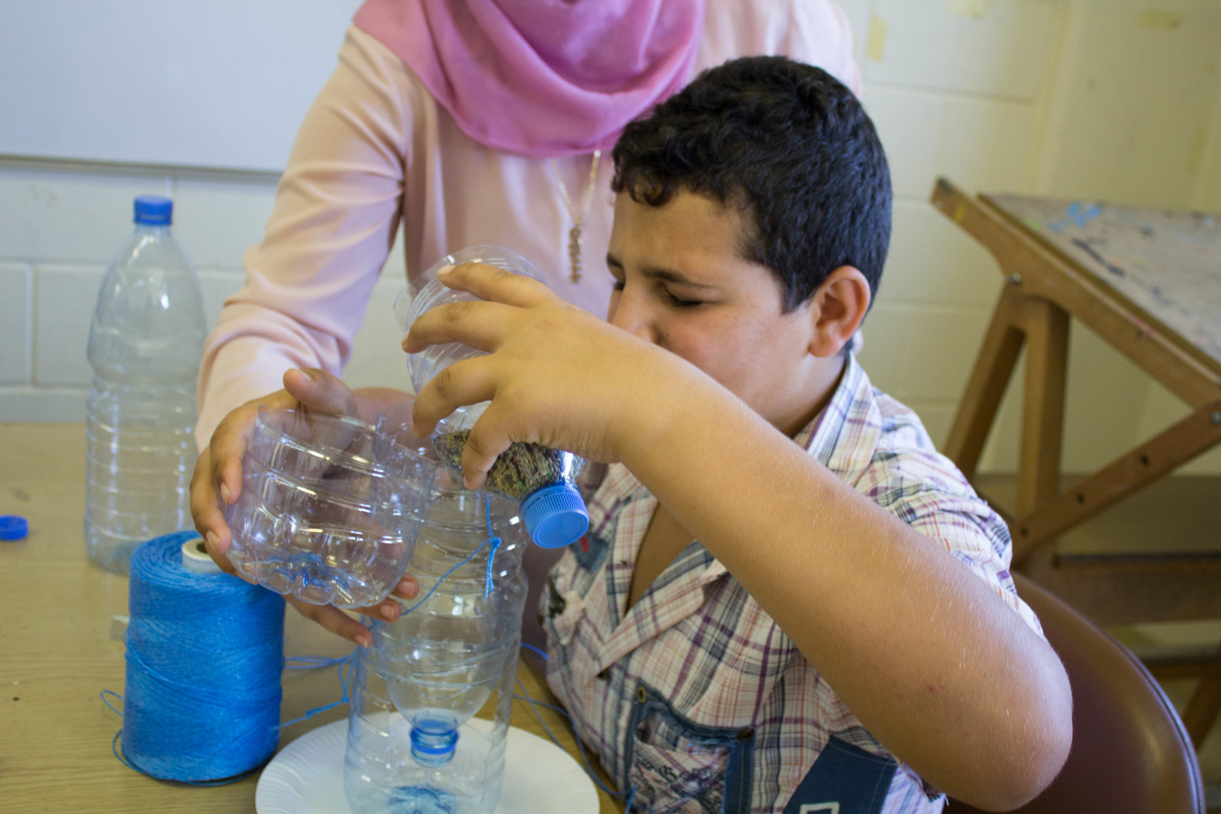 In this photo: a volunteer helps a blind student with a science experiment involving plastic bottles