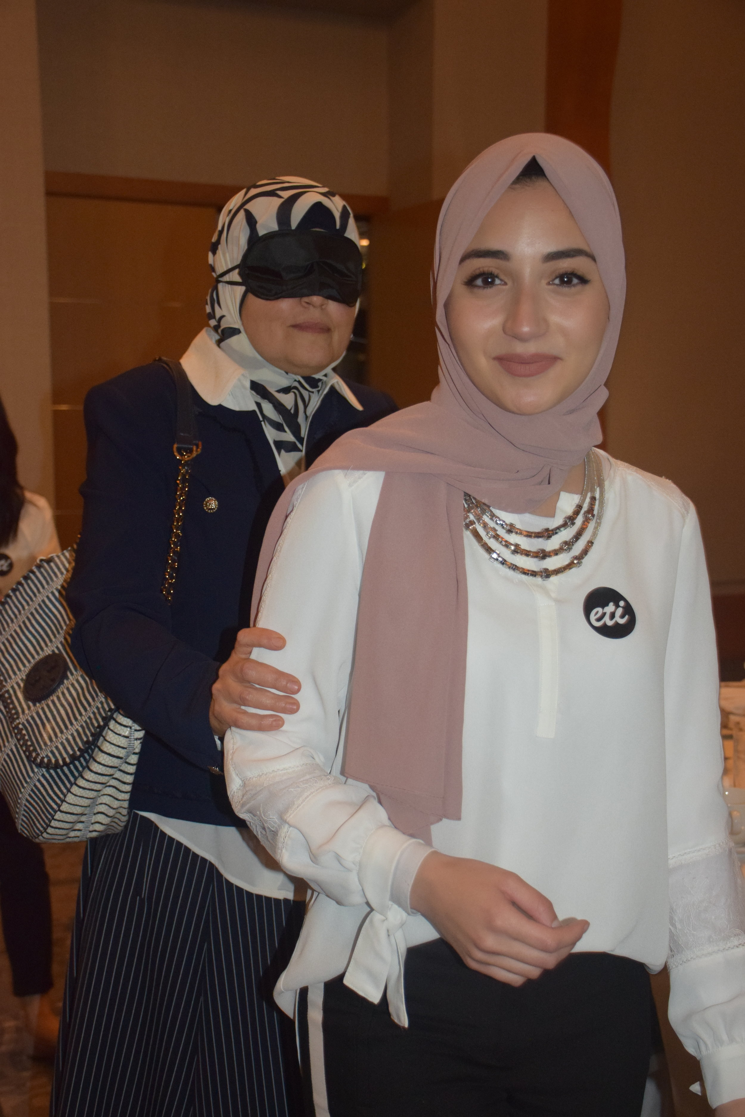 In this photo: An ETI sighted guide volunteer leads a blindfolded Dining in the Dark guest to her seat