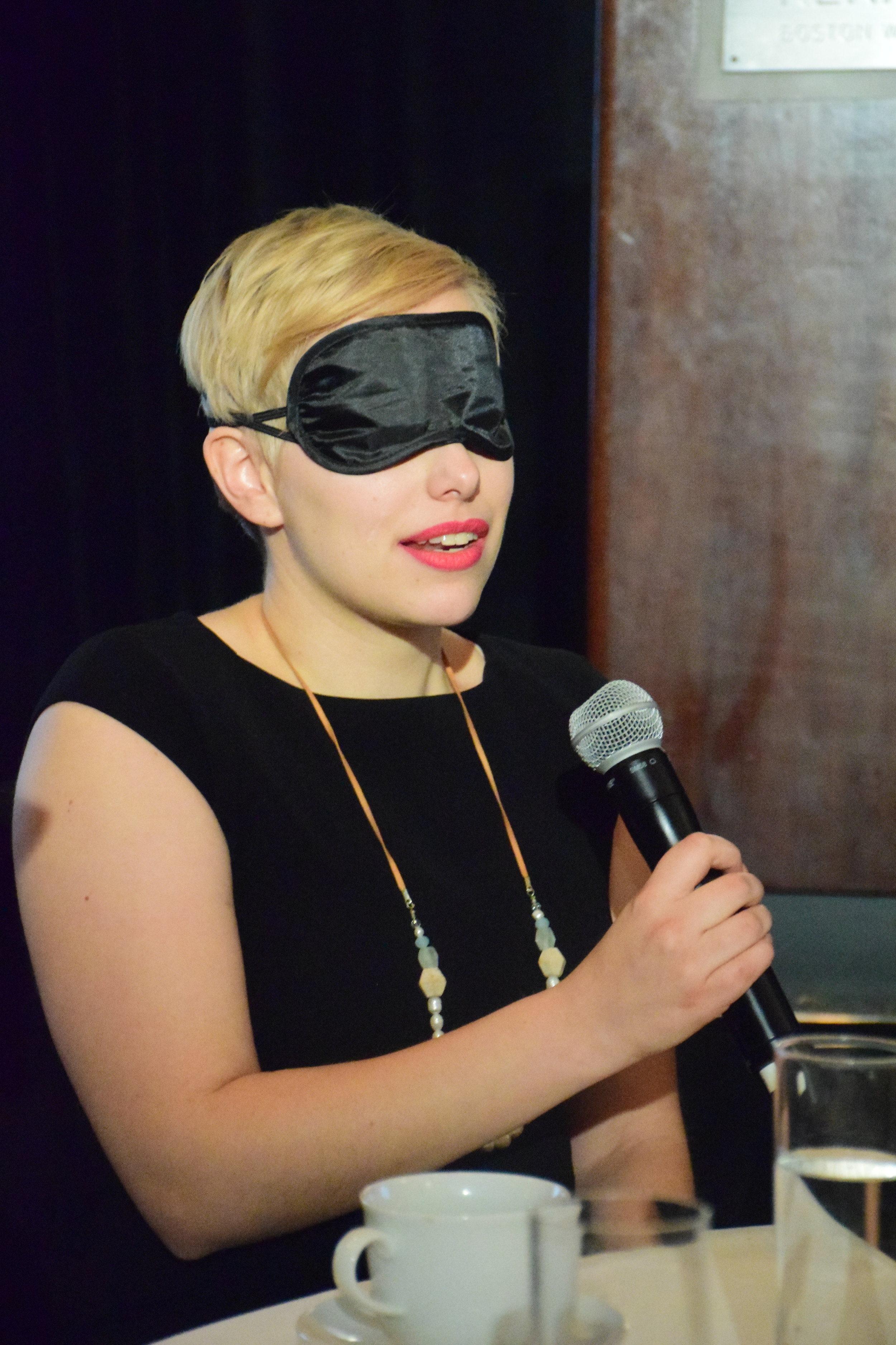 In this photo: A Dining in the Dark participant speaks into a microphone