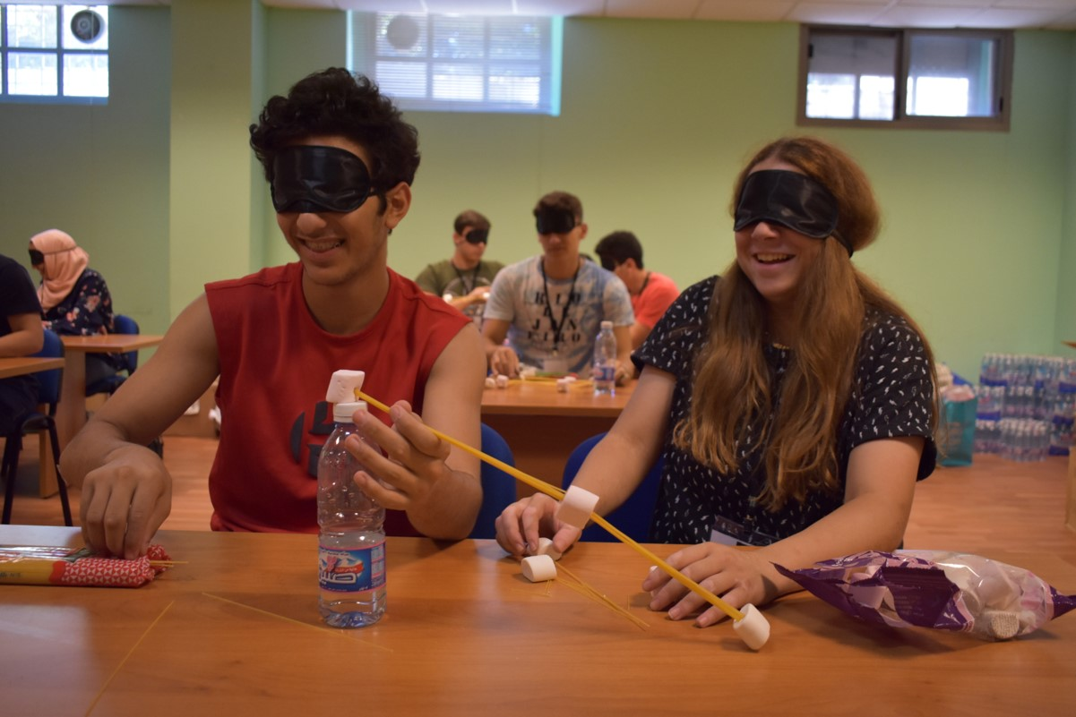 Blindfolded volunteers practicing science experiments (how to build a bridge)