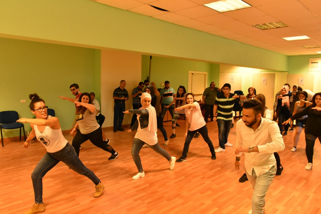Volunteers practicing capoeira moves with capoeira instructor
