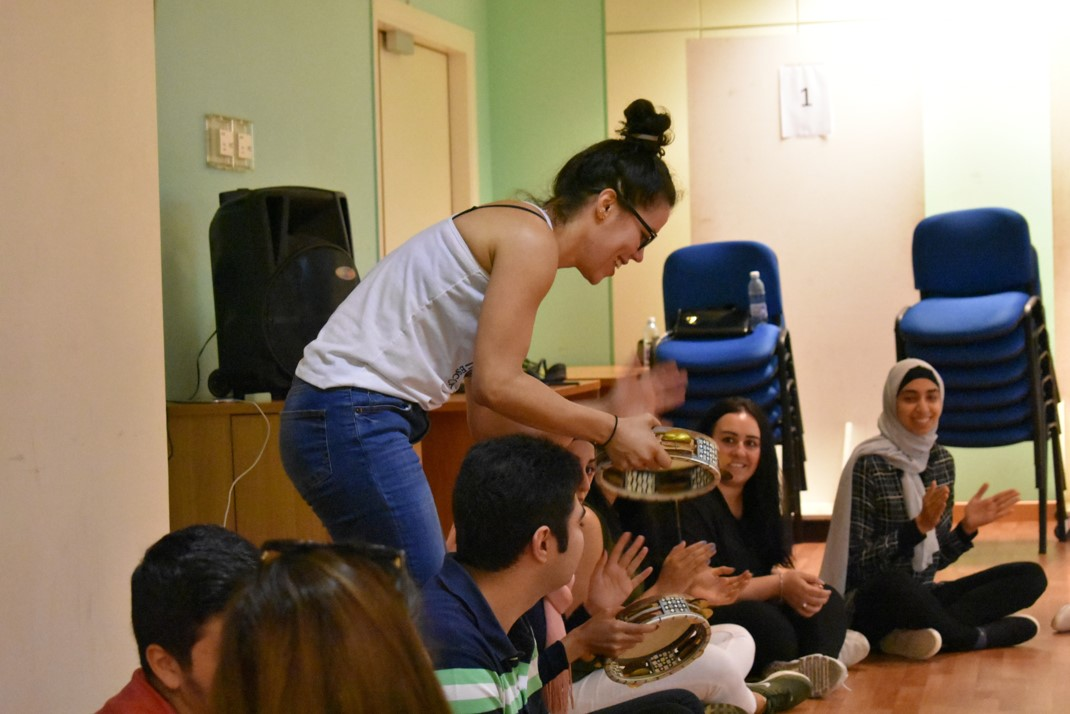 Capoeira instructor teaching volunteers how to use musical instruments during capoeira class