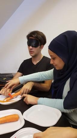 Volunteers training in ADL techniques (peeling vegetables)