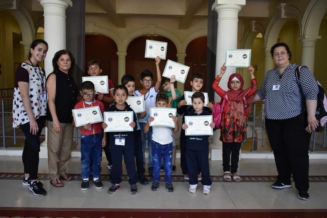 Visually impaired participants from group orange (ages 6 to 10) showing their certificates of participation, with Anna Barbosa, Edith Bitar from US Embassy, and volunteers