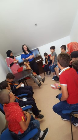 Visually impaired participants ages 6 to 10 sitting with volunteers during social literacy class