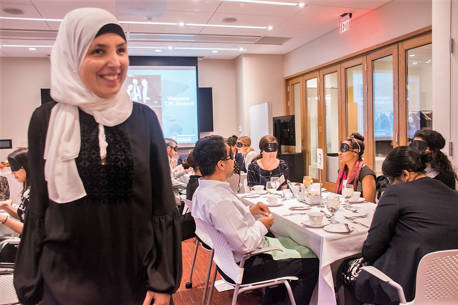 Sara Minkara, the session's facilitator, stands smiling ear to ear as she overhears the insightful conversations taking place around the room. Blindfolded participants sit at tables around Sara.