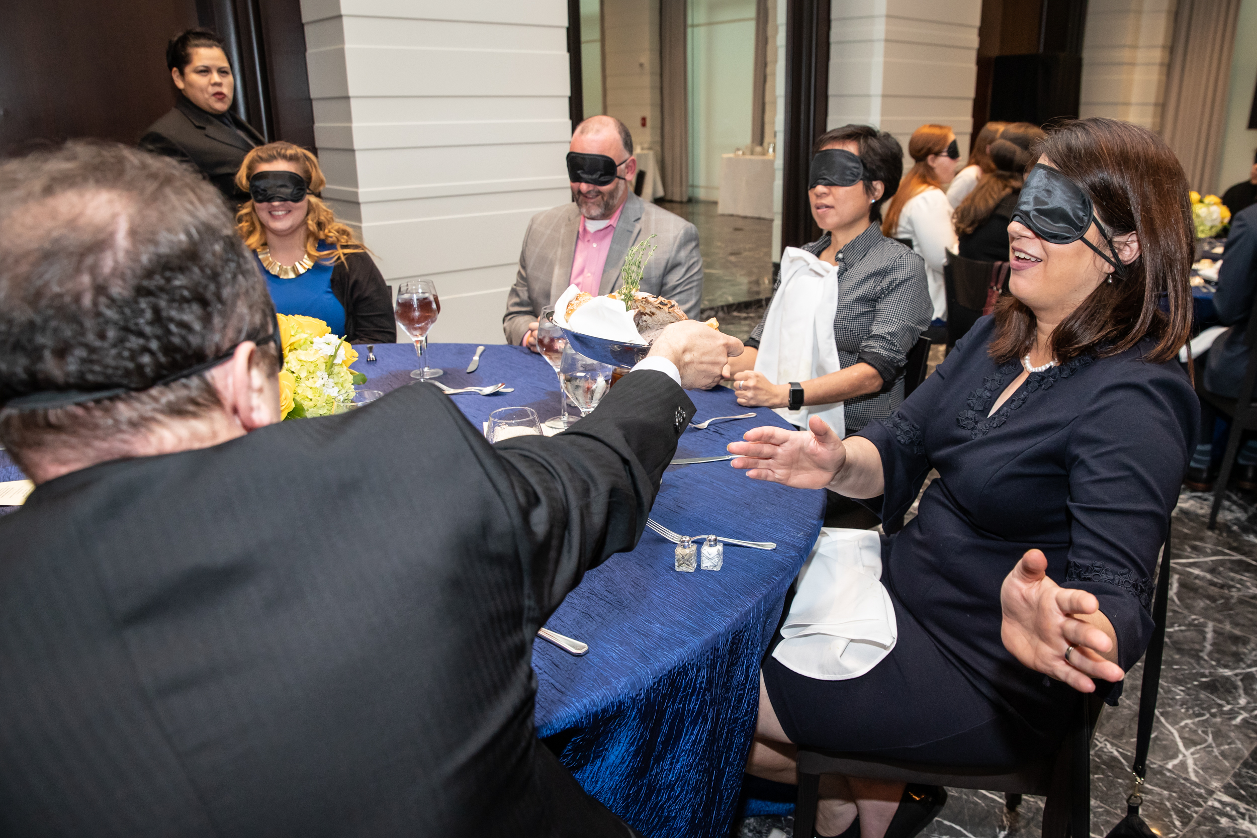 Five blindfolded participants sit at a round table, with more participants out of frame. One participant passes a bread basket toward the participant on his right. She reaches out to find the bread.