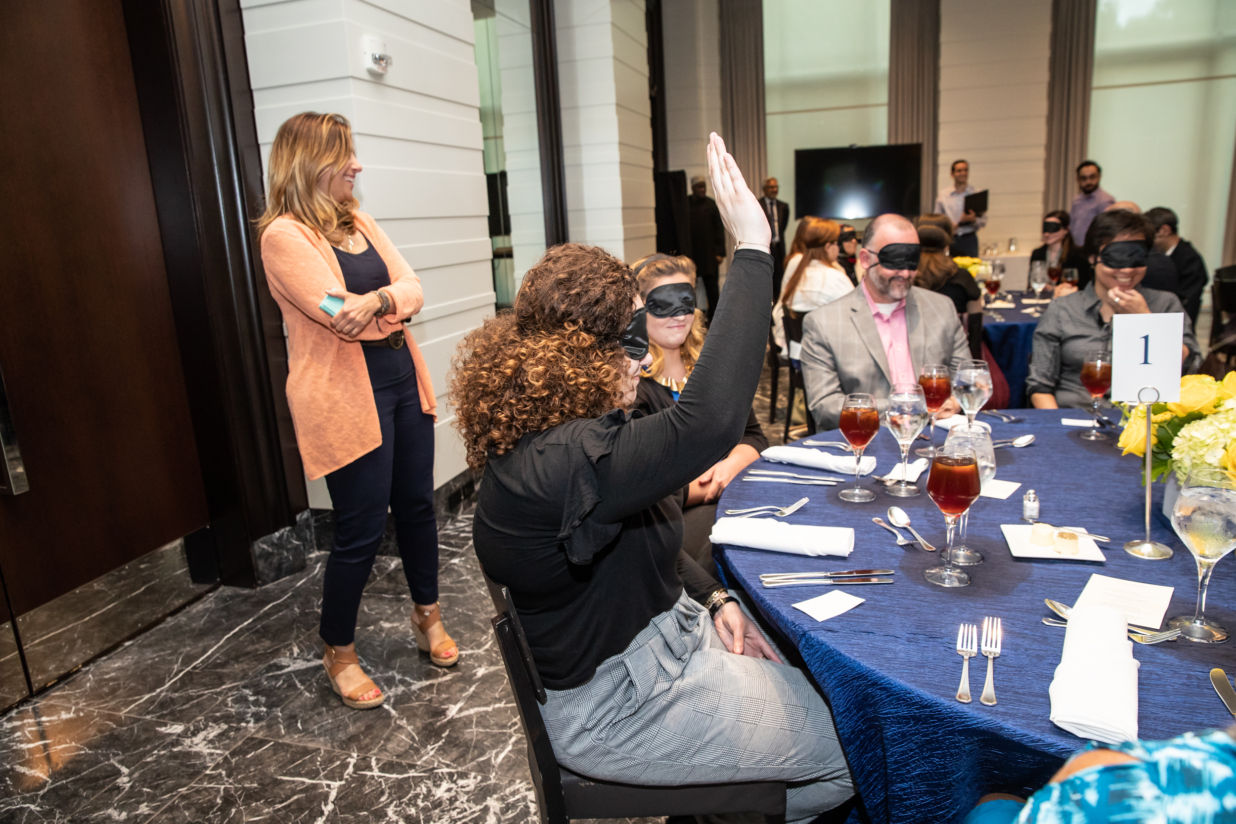 A blindfolded participant raises her hand to share with the room her favorite part of event.
