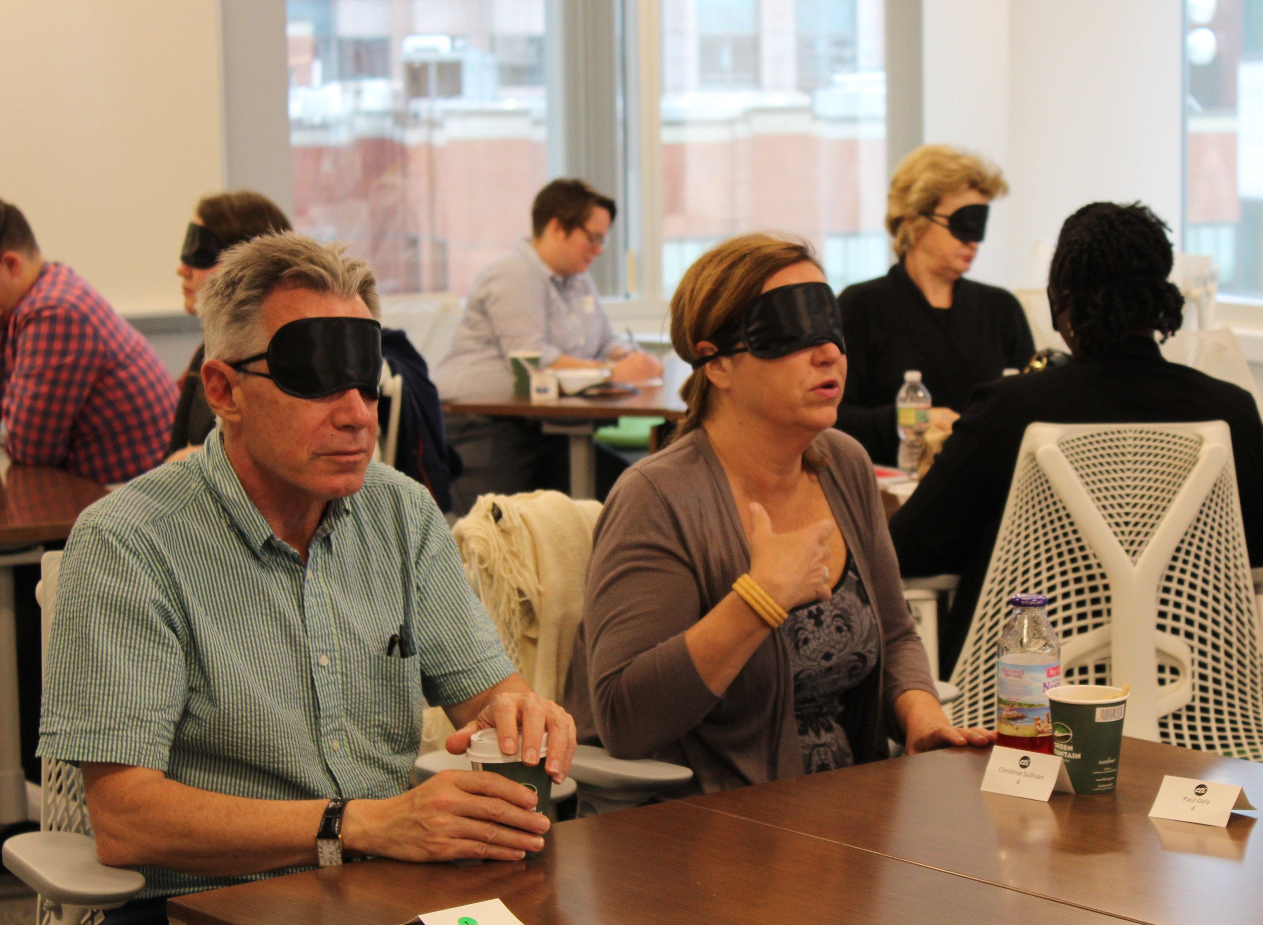 A blindfolded participant shares with her table. Another participants sitting to her right listens intently.