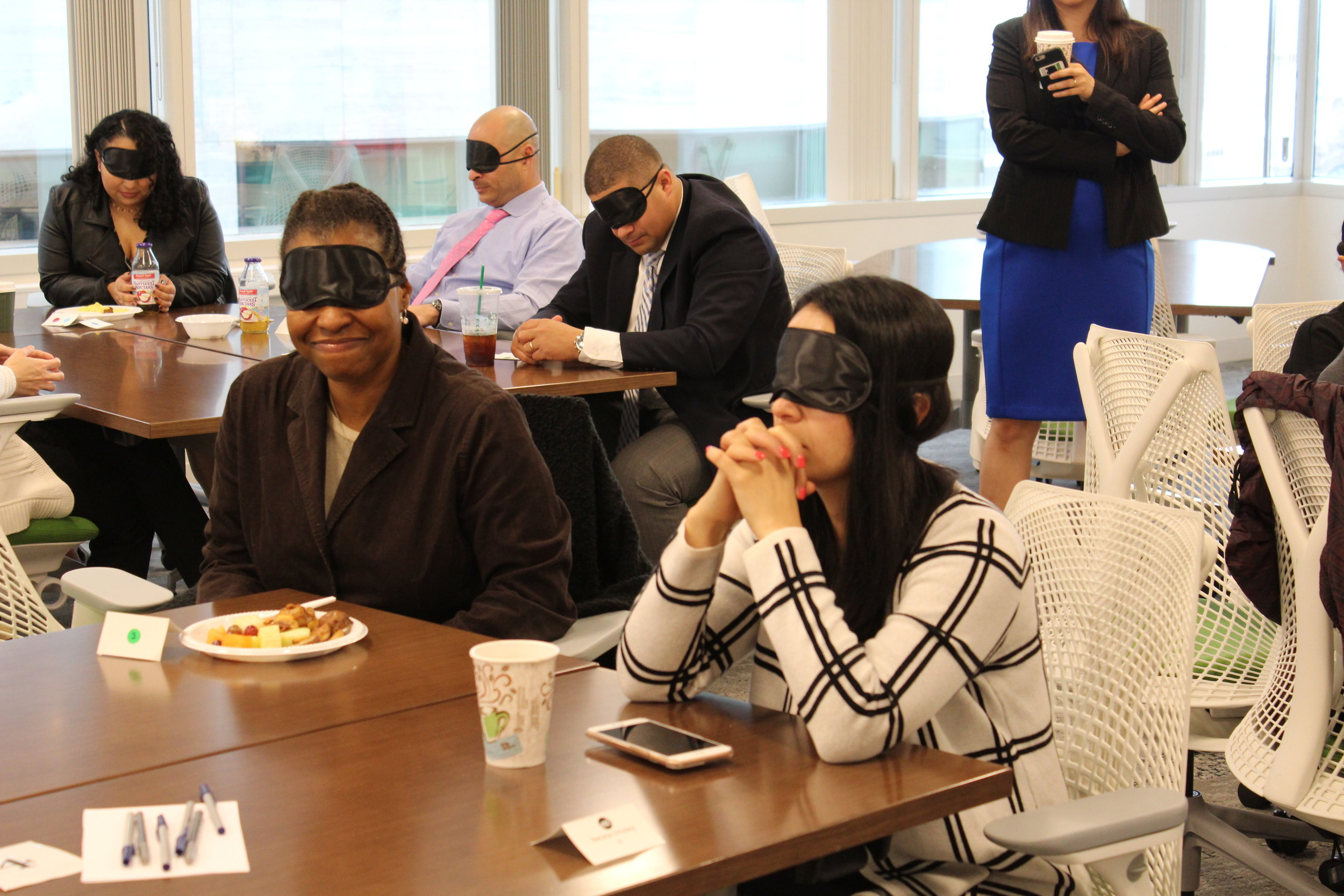 Blindfolded participants sit and listen to facilitates prompts. Two participants sit at a table in the foreground and three participants sit at a table in the background.