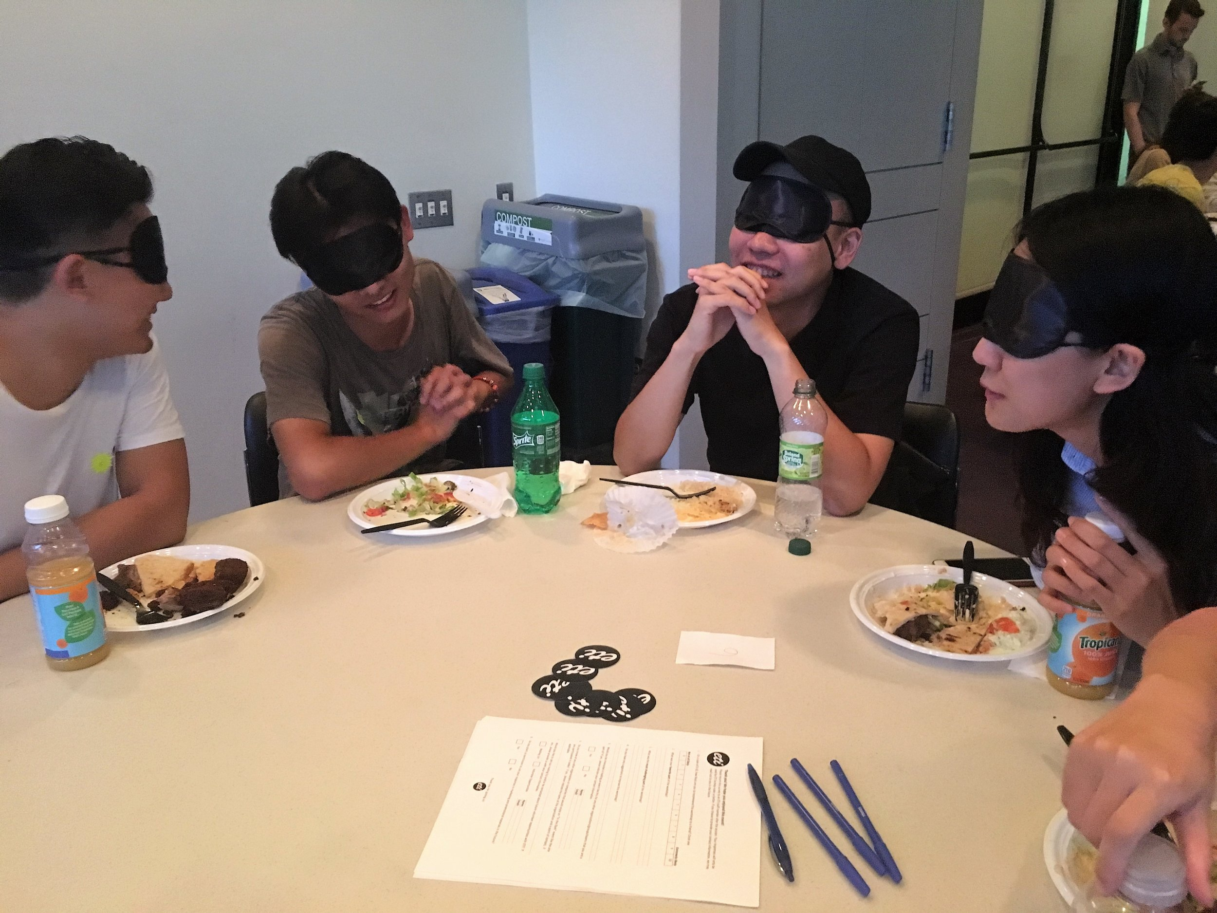 Four blindfolded participants sit at a round table, laughing and talking with plates of food in front of them.