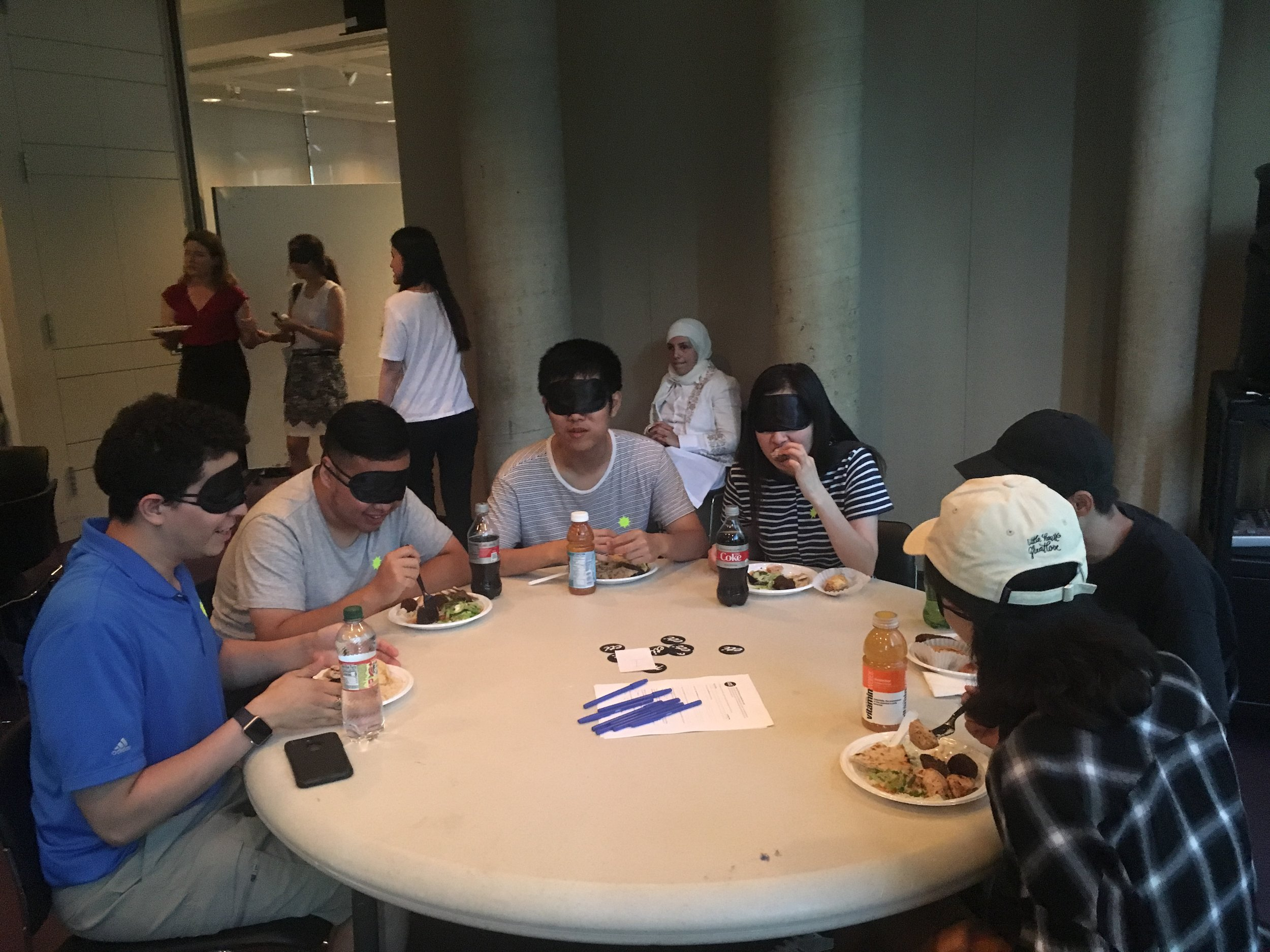 Six participants sit around a round table, eating and making conversation. In the background, a sighted guide leads a blindfolded participant to their seat.