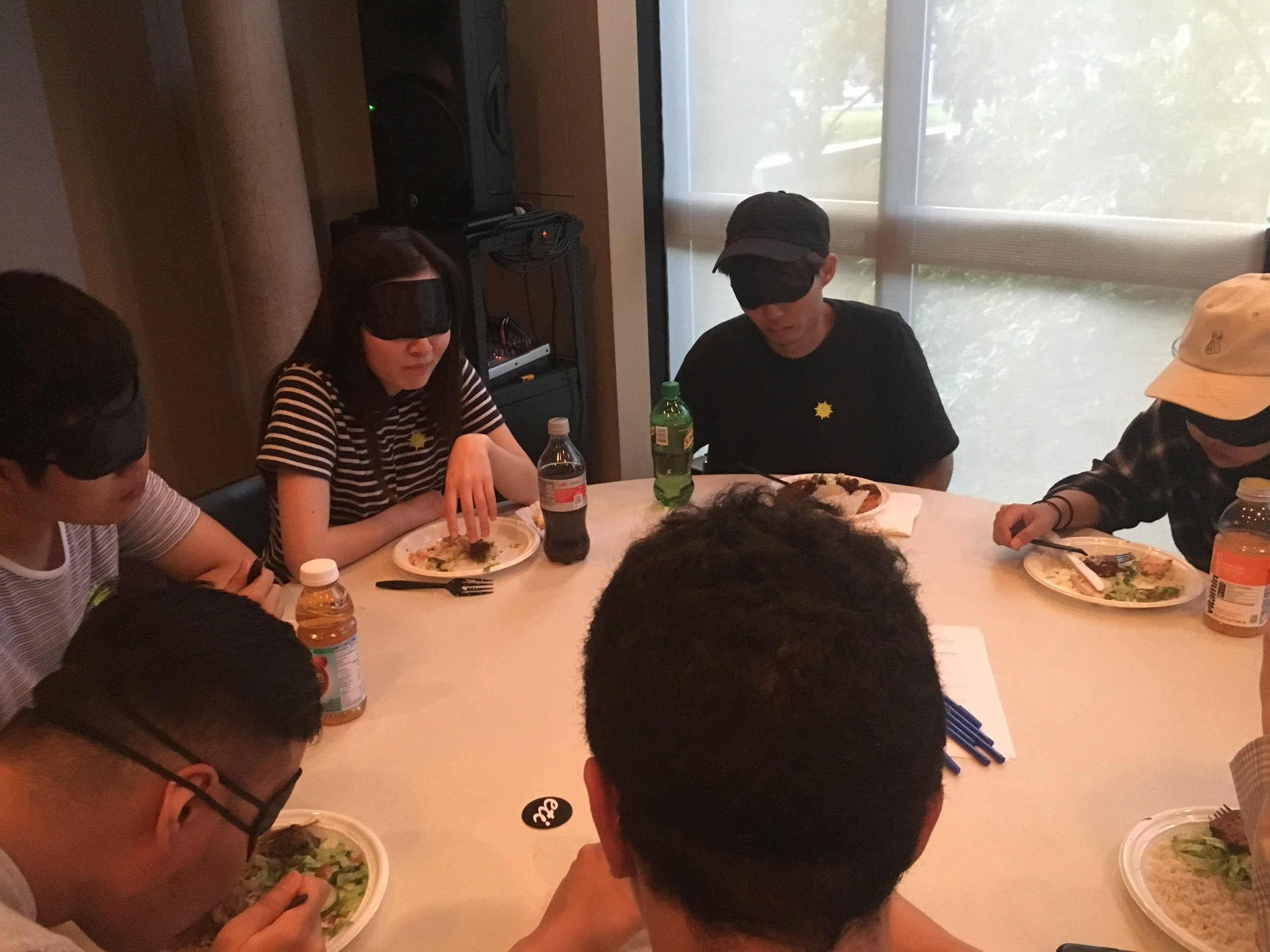 A blindfolded participant gestures with her hand as she makes a comment to the six other people sitting at her table.