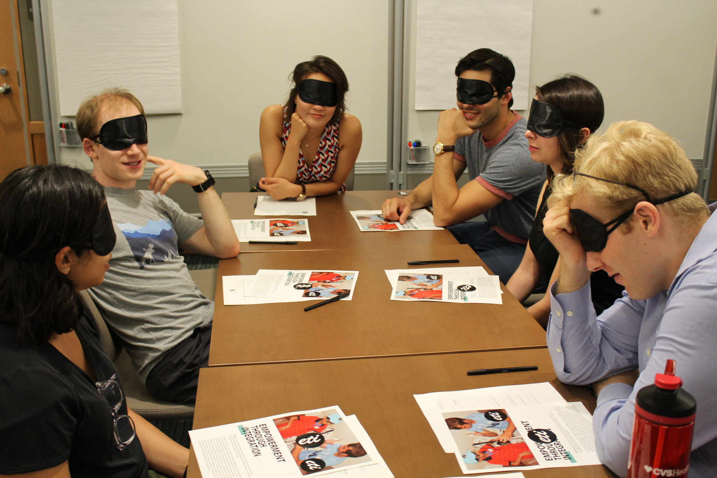 Six blindfolded participants sit around a table and think about the questions posed by the facilitator.
