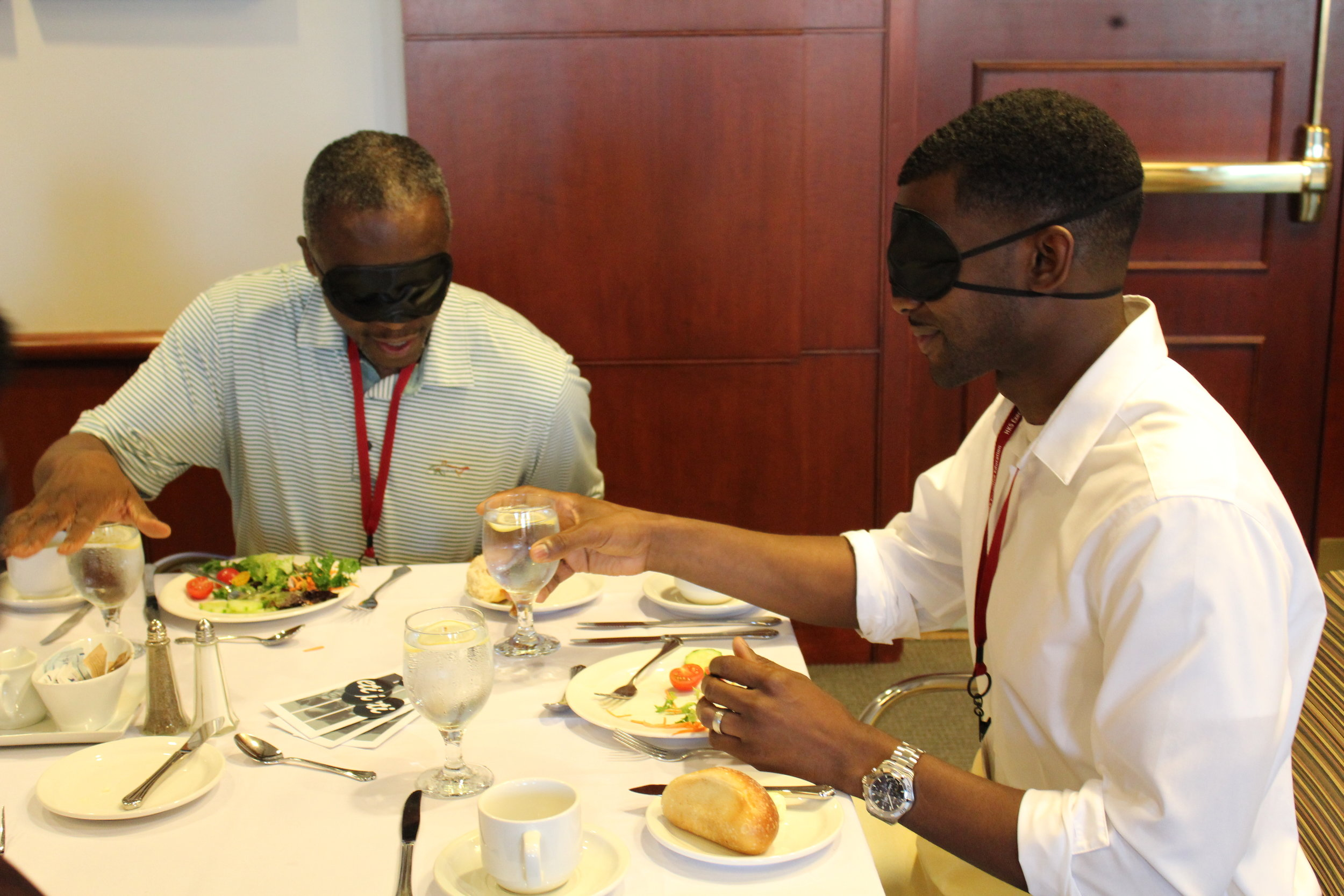 Two blindfolded participants sit at a table and try to locate their own glasses of water during their meal.