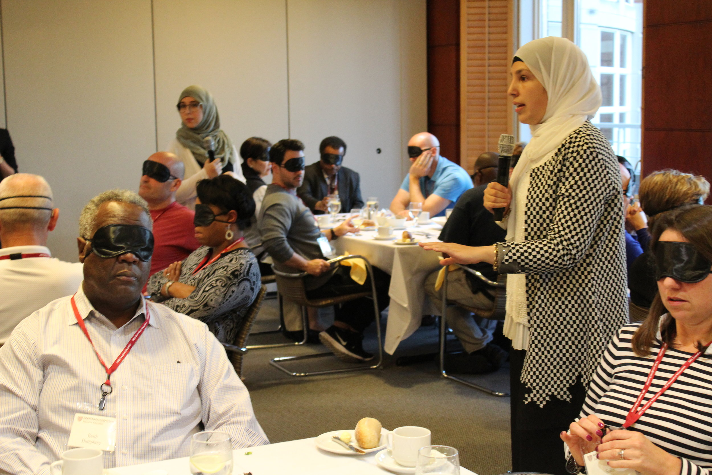 Founder and CEO Sara Minkara speaks into a microphone, facilitating a discussion in a room full of blindfolded participants.