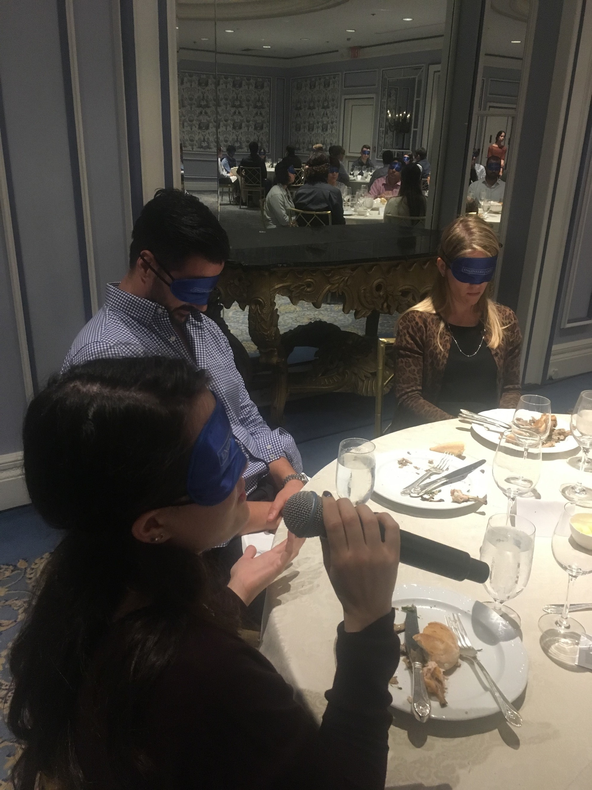 Blindfolded woman sitting at a table answering a question while other blindfolded participants are listening