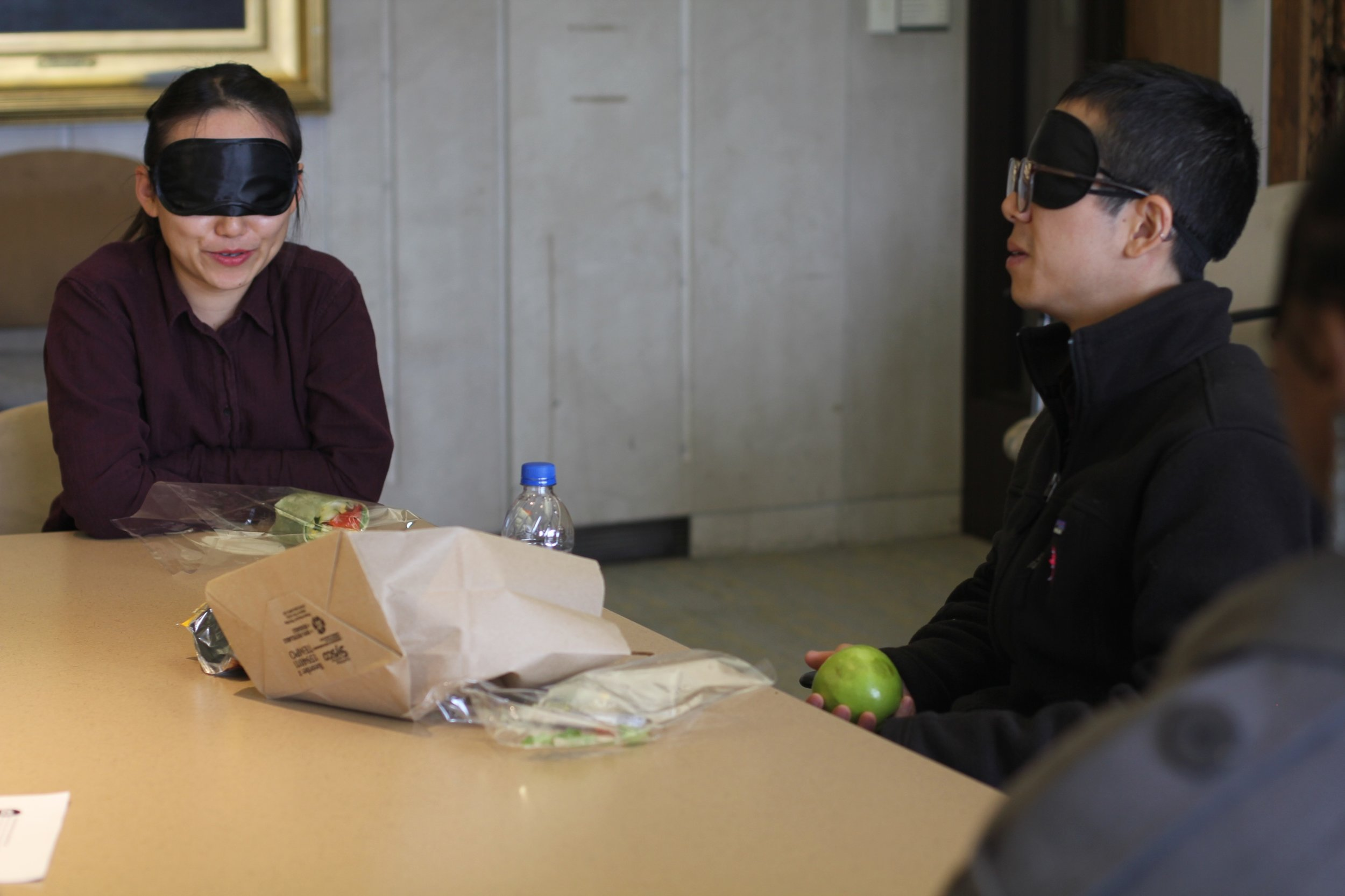 Two blindfolded participants conversing while eating at a table