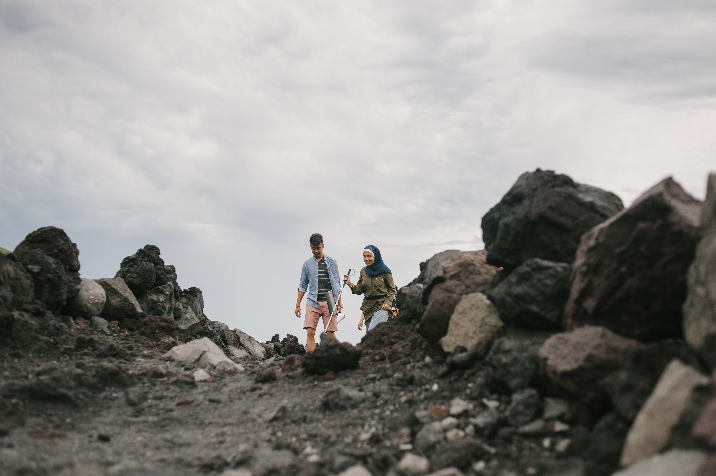 A man and a woman walk on a rocky path. The woman holds a white can and is smiling.