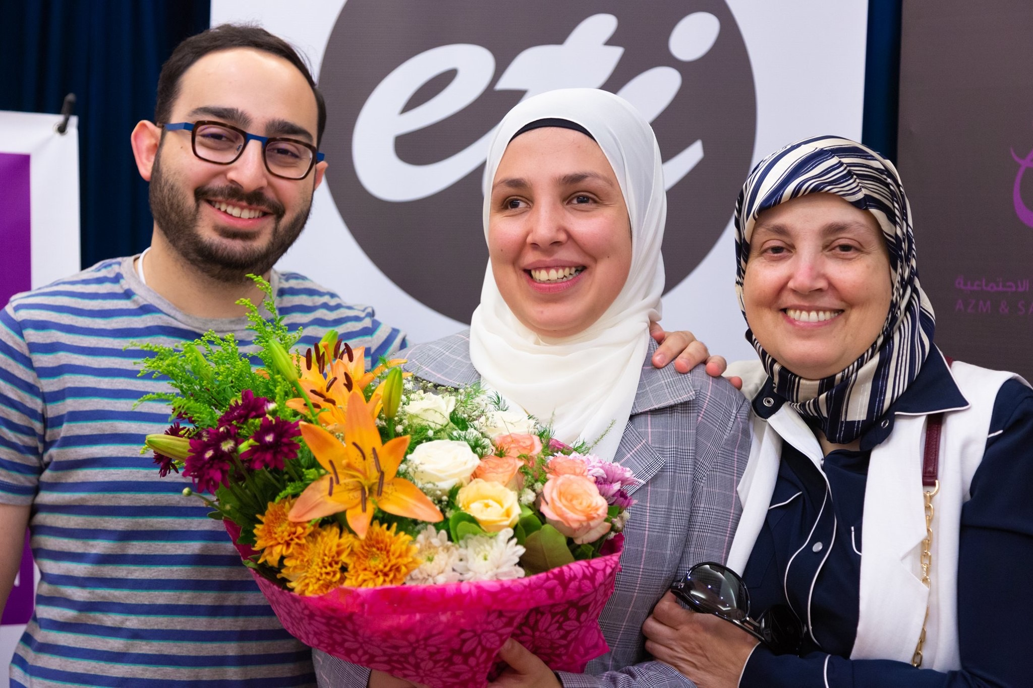 """Two women and a man stand in front of a sign that reads """"ETI"""" All three are smiling brightly. The woman in the middle holds a bright bouquet of flowers, The vibrant flowers illustrate the affection and pride that Sara's family has for her."""