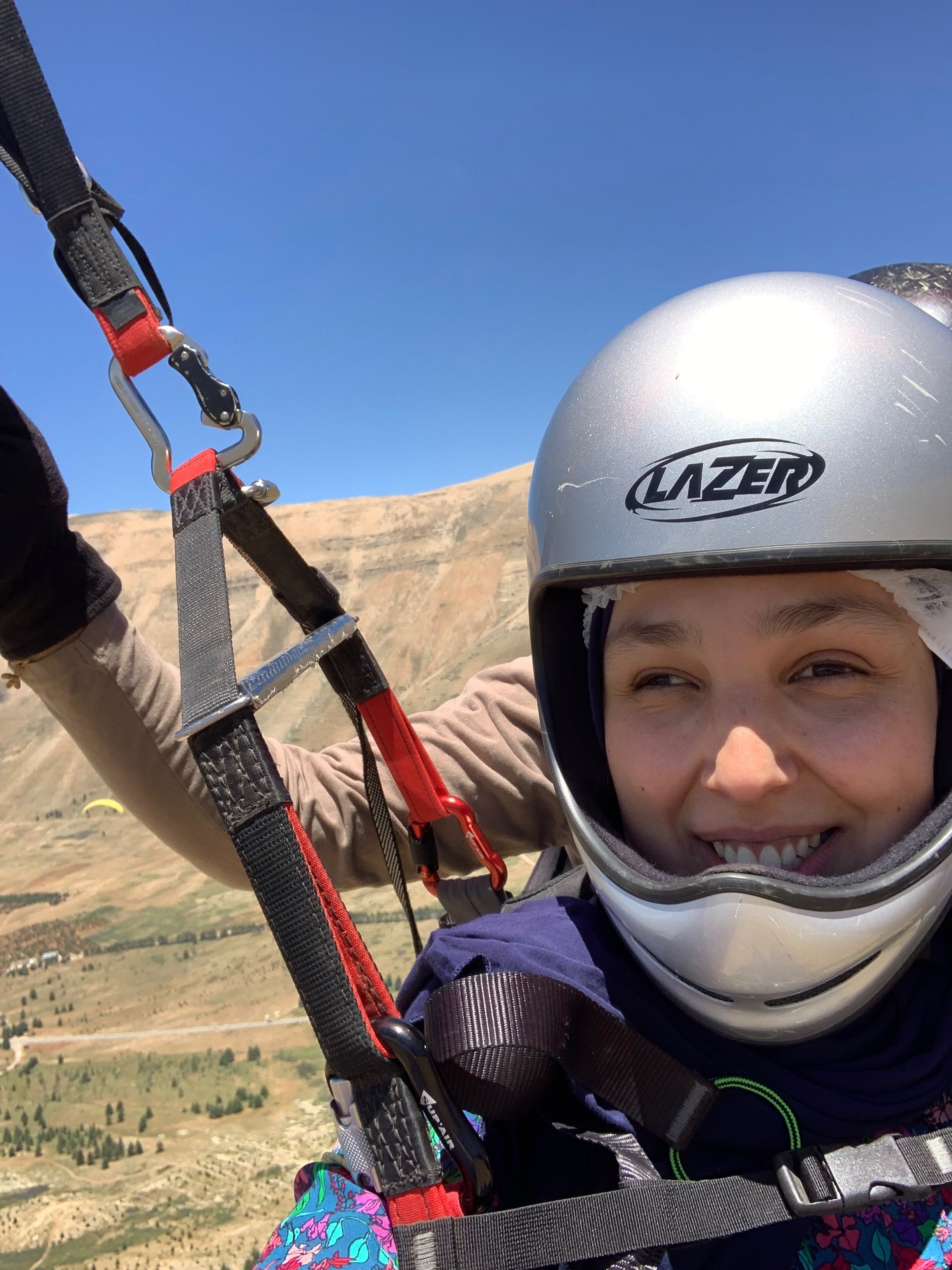 A close up image shows a woman smiling at the camera, wearing a silver helmet and with straps and clips covering her chest. Behind her we see the hand of a guide controlling levers. The background is a beautiful valley.